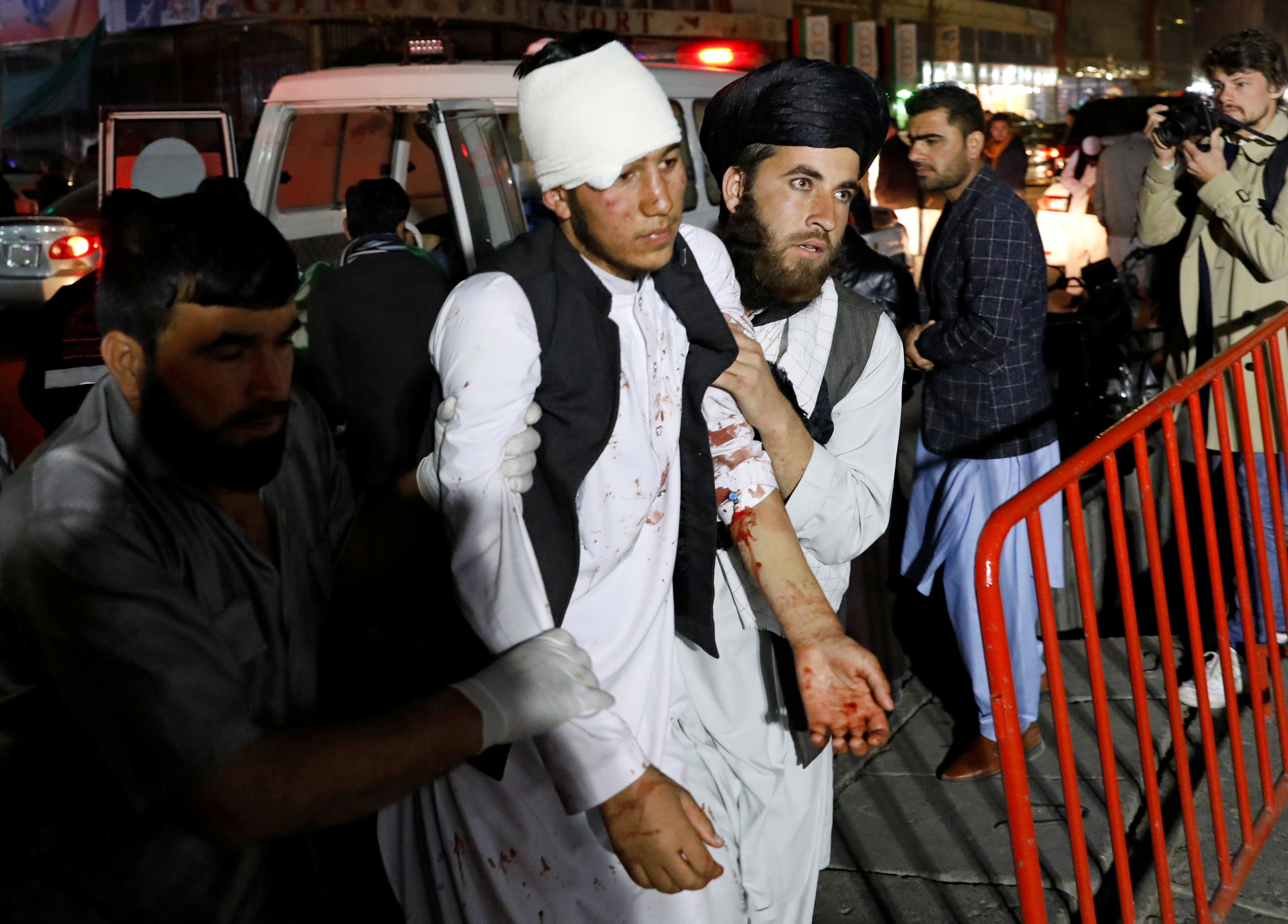 Afghan men carry an injured person to a hospital after a suicide attack in Kabul, Afghanistan, Nov. 20, 2018.