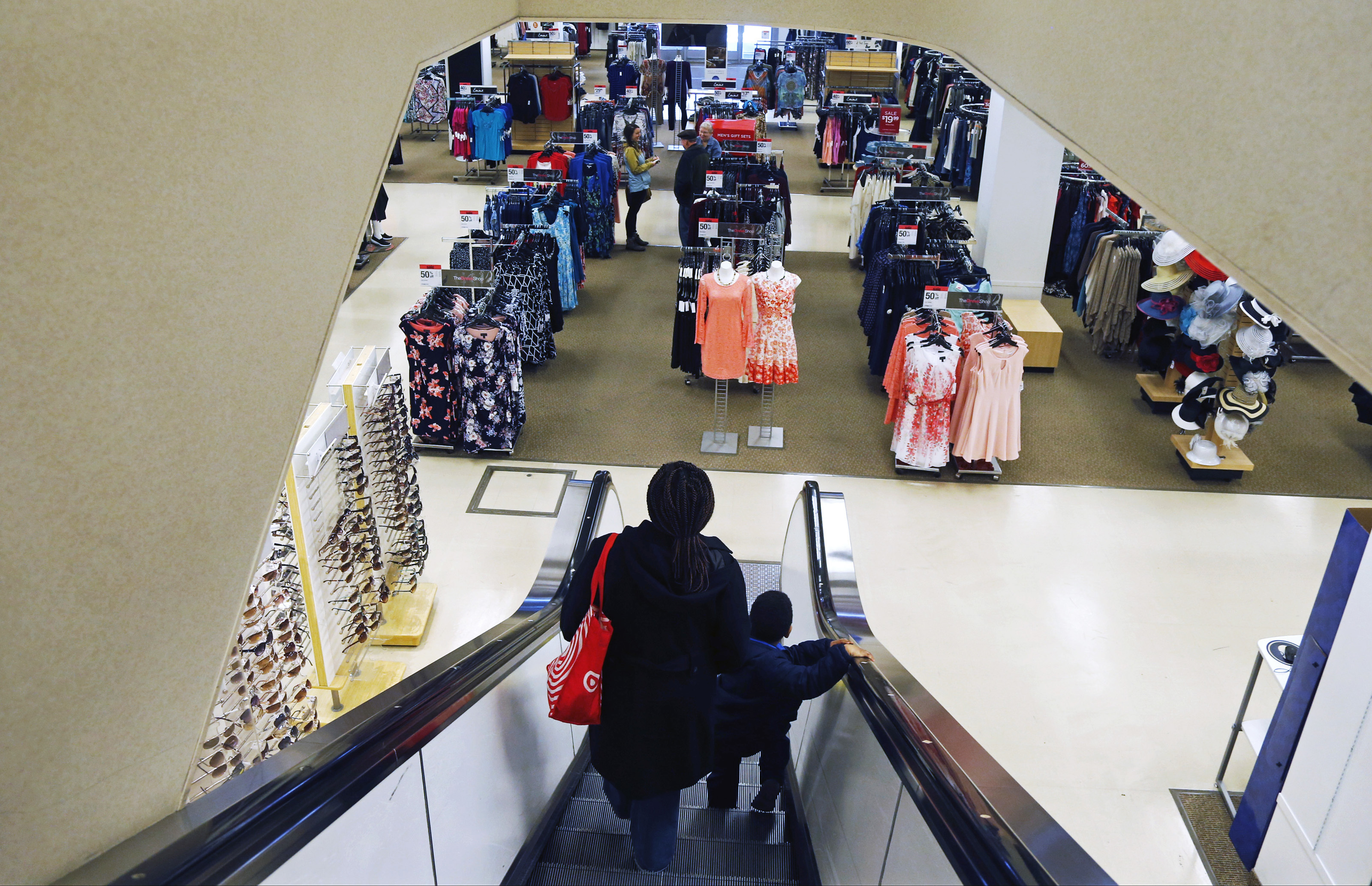 In this March 22, 2017, file photo, a woman and child ride the escalator at a Sears store in St. Paul, Minn.  Sears has filed for Chapter 11 bankruptcy protection Monday, Oct. 15, 2018.