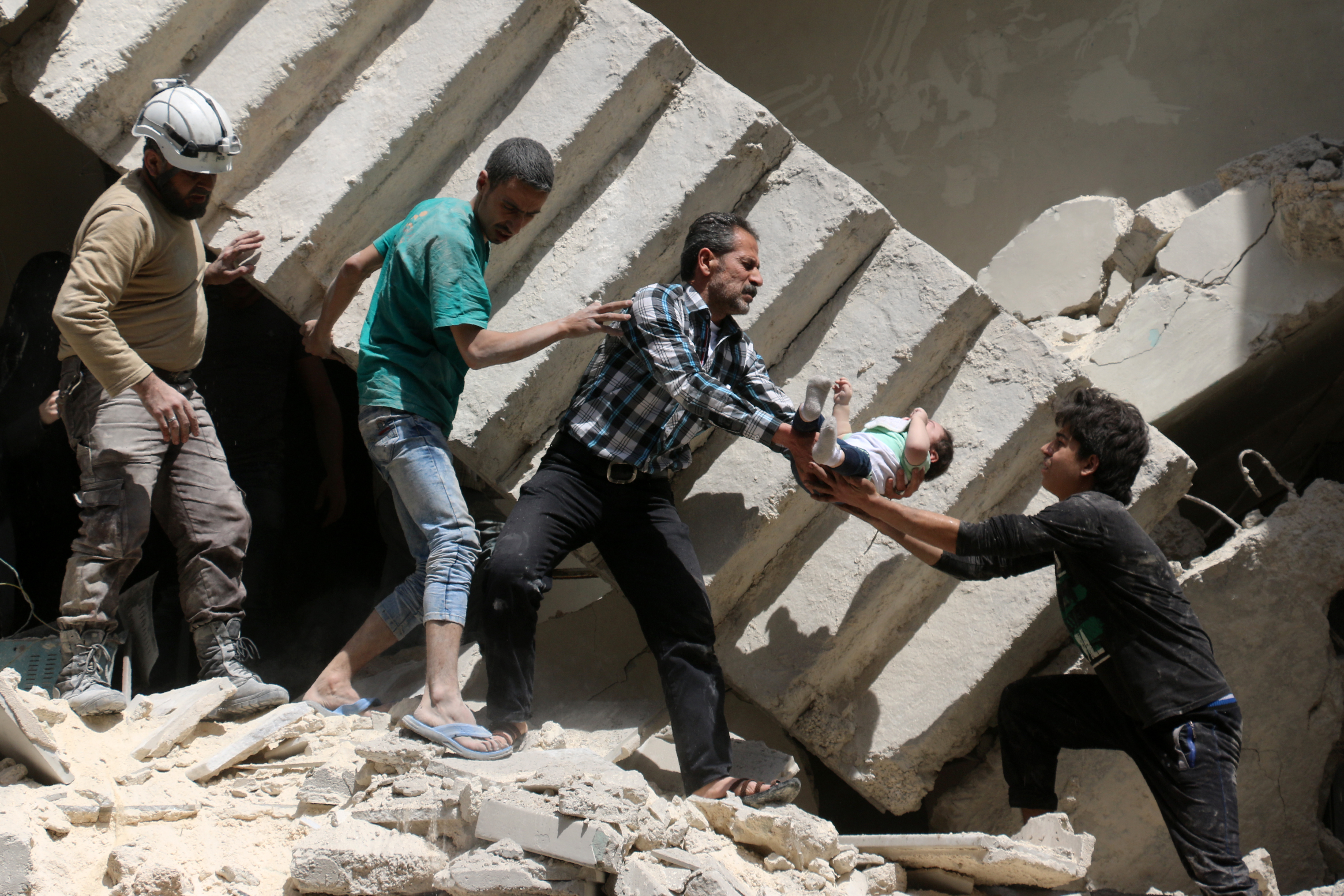 Syrian civil defence volunteers and rescuers remove a baby from under the rubble of a destroyed building following a reported air strike on the rebel-held neighbourhood of al-Kalasa in the northern Syrian city of Aleppo, on April 28, 2016.