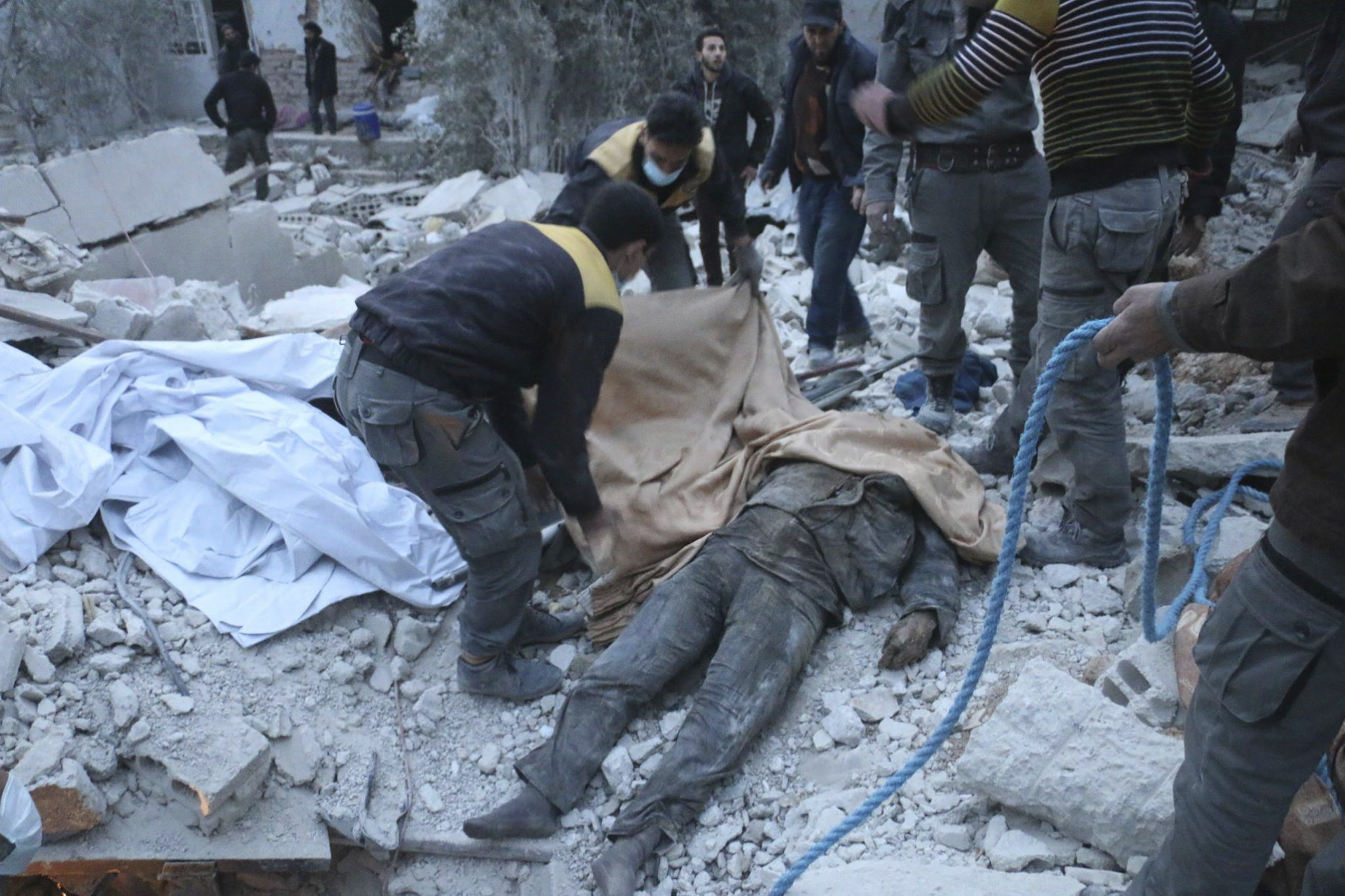 FILE - This photo released Feb. 20, 2018, by the Syrian civil defense group known as the White Helmets shows members of the group removing a victim from under the rubble of a damaged shelter that was attacked during airstrikes and shelling by Syrian ...