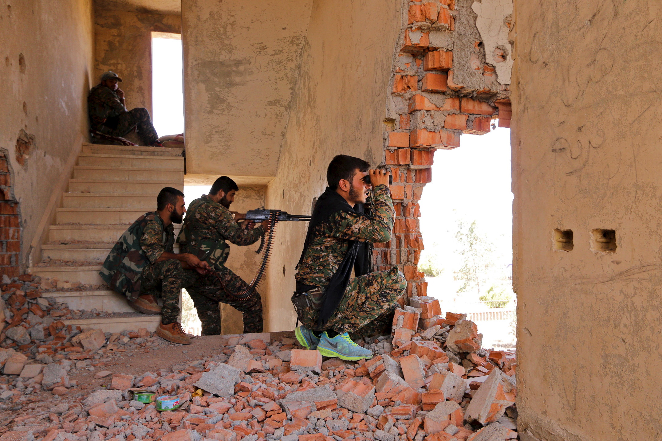 Kurdish People's Protection Units (YPG) fighters take up positions inside a damaged building in al-Vilat al-Homor neighborhood in Hasaka city, as they monitor the movements of Islamic State fighters who are stationed in Ghwayran neighborhood in Hasak...