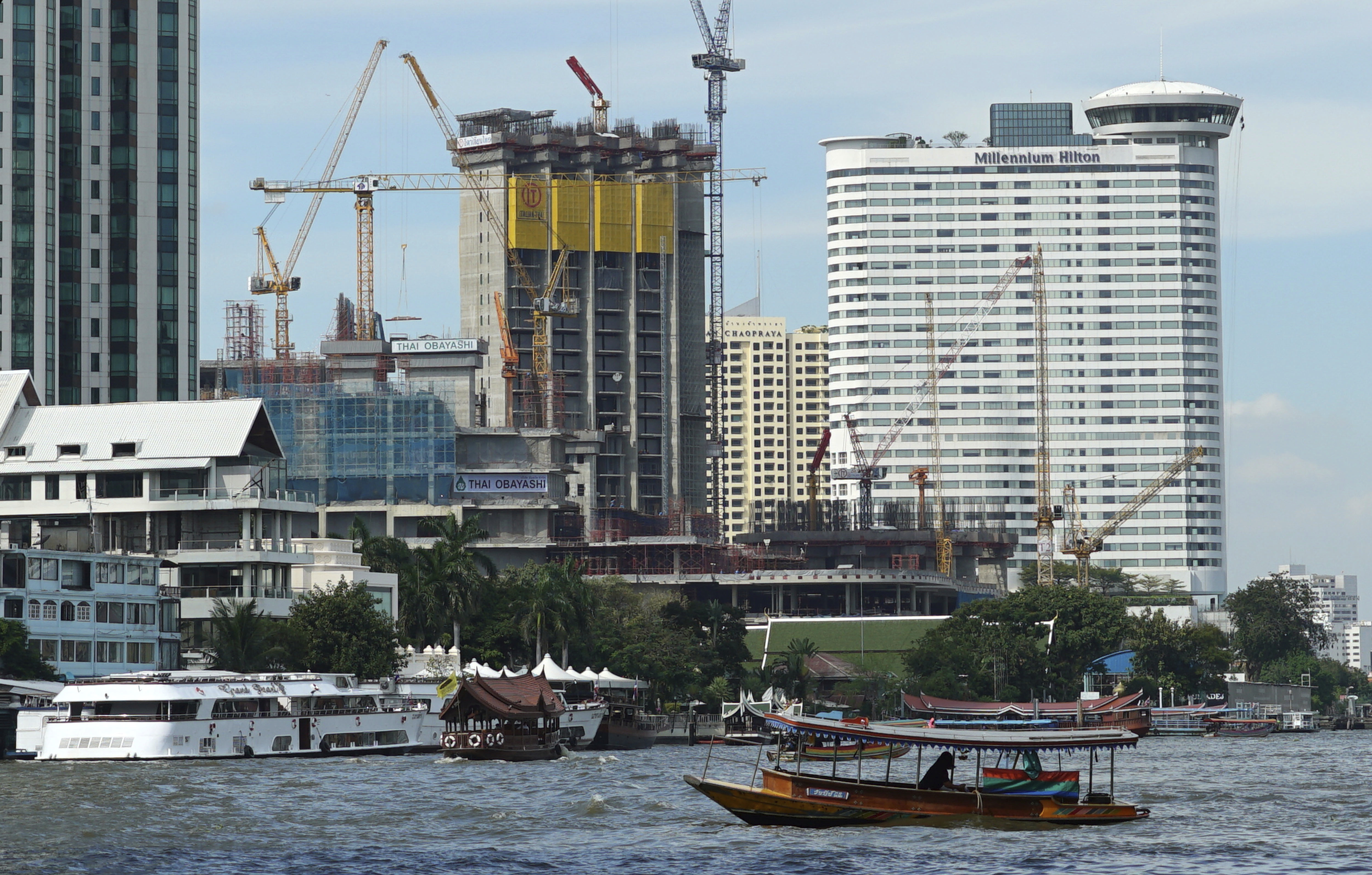 FILE - A riverboat taxi crosses the Chao Phraya river in front of massive construction projects, Jan. 18, 2017, in Bangkok, Thailand.
