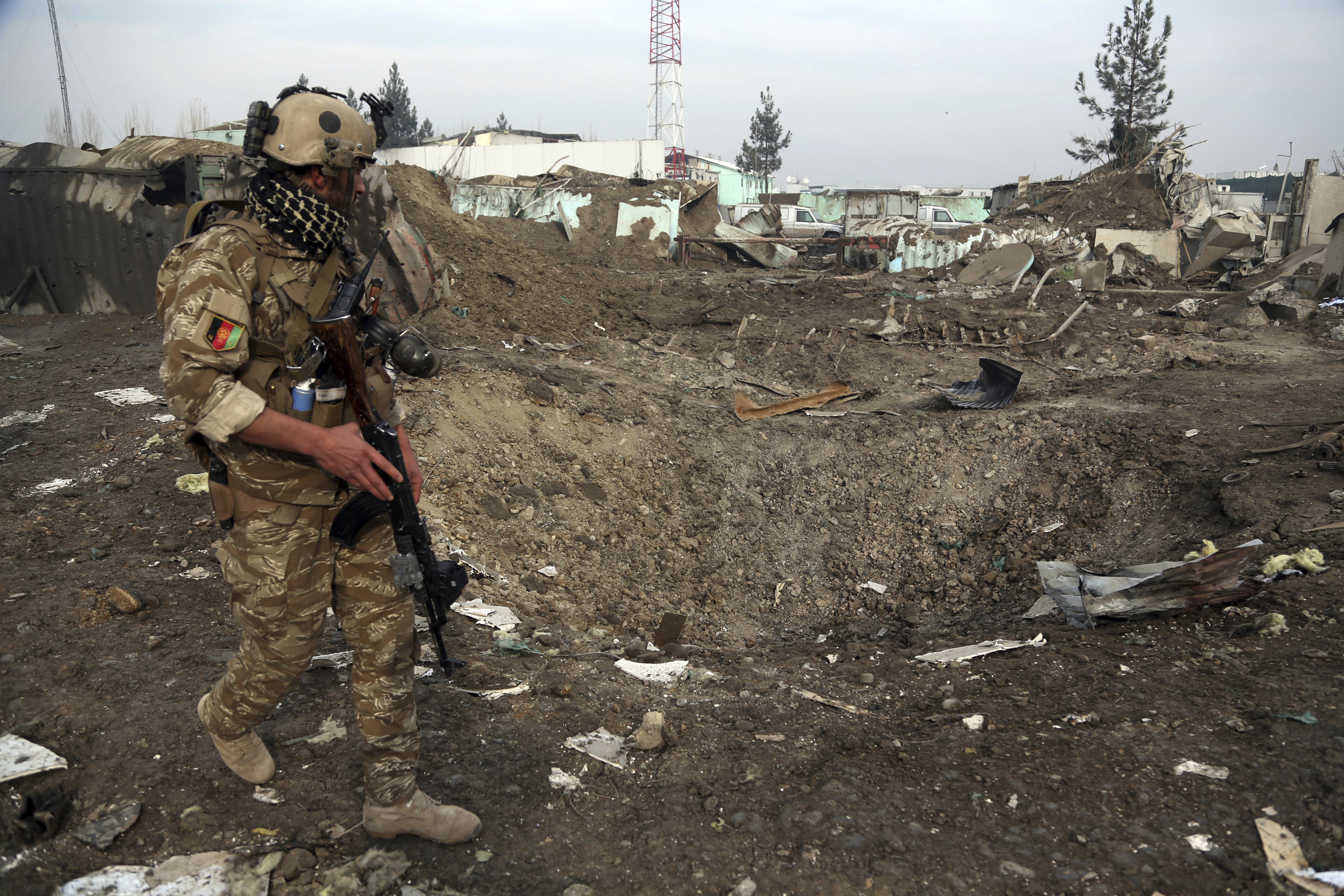 An Afghan security forces member walks next to a crater caused by a suicide bomb attack in Kabul, Afghanistan, Nov. 29, 2018.
