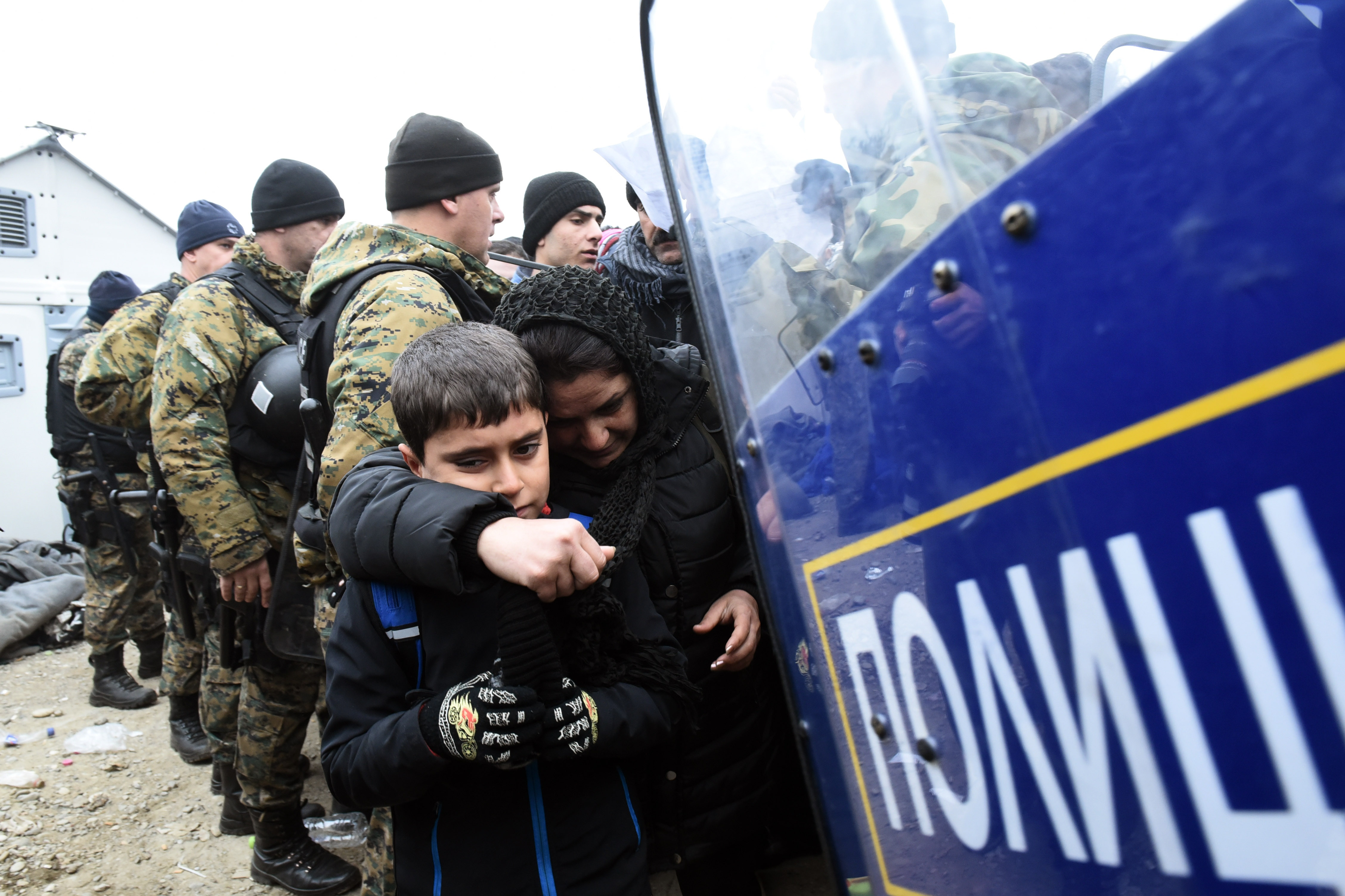 Macedonian policemen stand guard as a woman and a kid pass from the northern Greek village of Idomeni to southern Macedonia, Nov. 20, 2015.