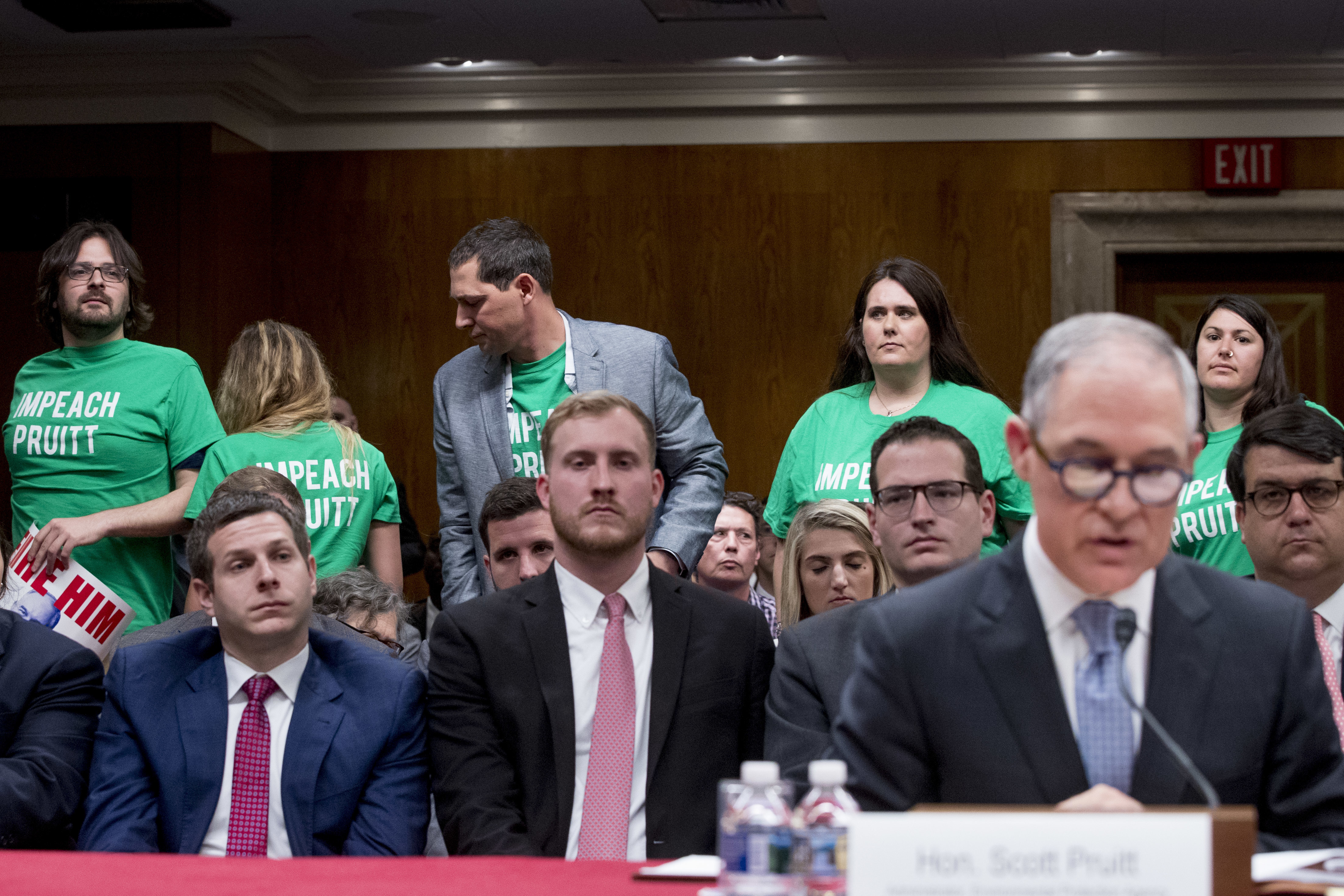 """Members of the audience wear shirts that read """"Impeach Pruitt"""" as EPA Administrator Scott Pruitt, right, testifies before a Senate Appropriations subcommittee on budget on Capitol Hill in Washington,  May 16, 2018."""