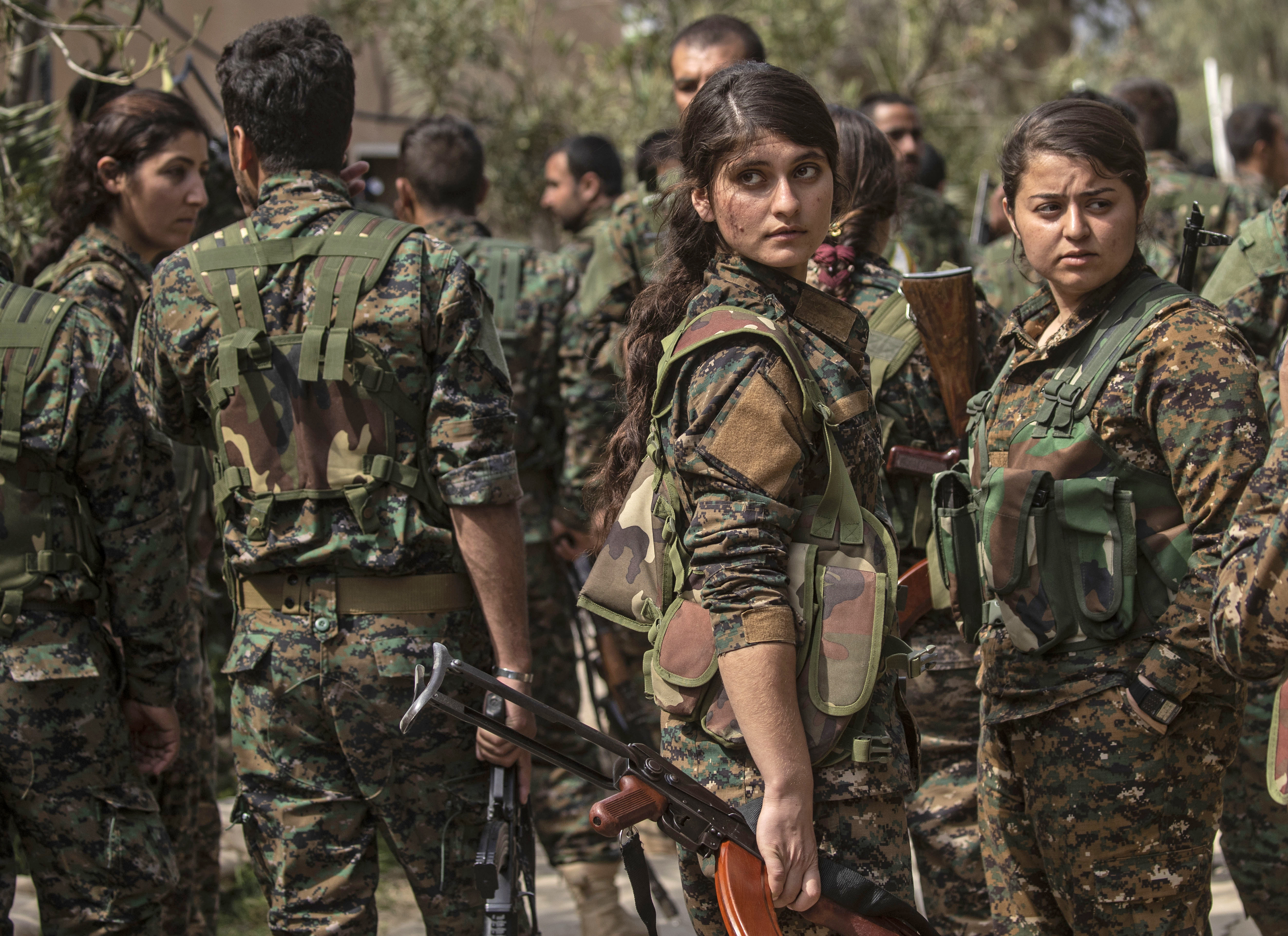 Fighters of the U.S.-backed Kurdish-led Syrian Democratic Forces (SDF), including women, dance as they celebrate near the Omar oil field in the eastern Syrian Deir Ezzor province, March 23, 2019, after announcing the total elimination of the Islamic ...