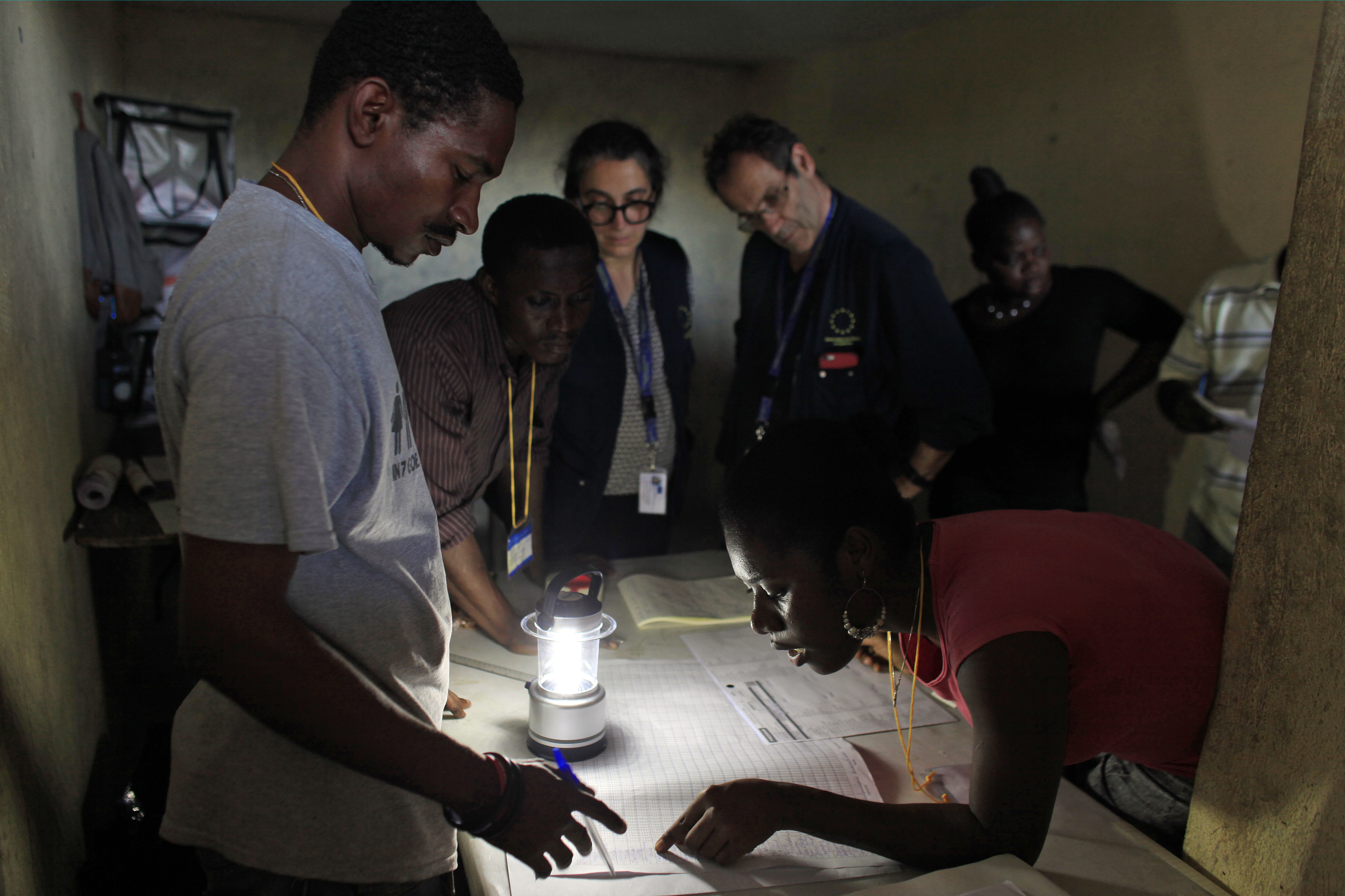 Members of the European Union Election Observation Mission, behind, observe electoral workers count ballots at a polling station at the end of the national elections in Port-au-Prince, Haiti, Oct. 25, 2015.