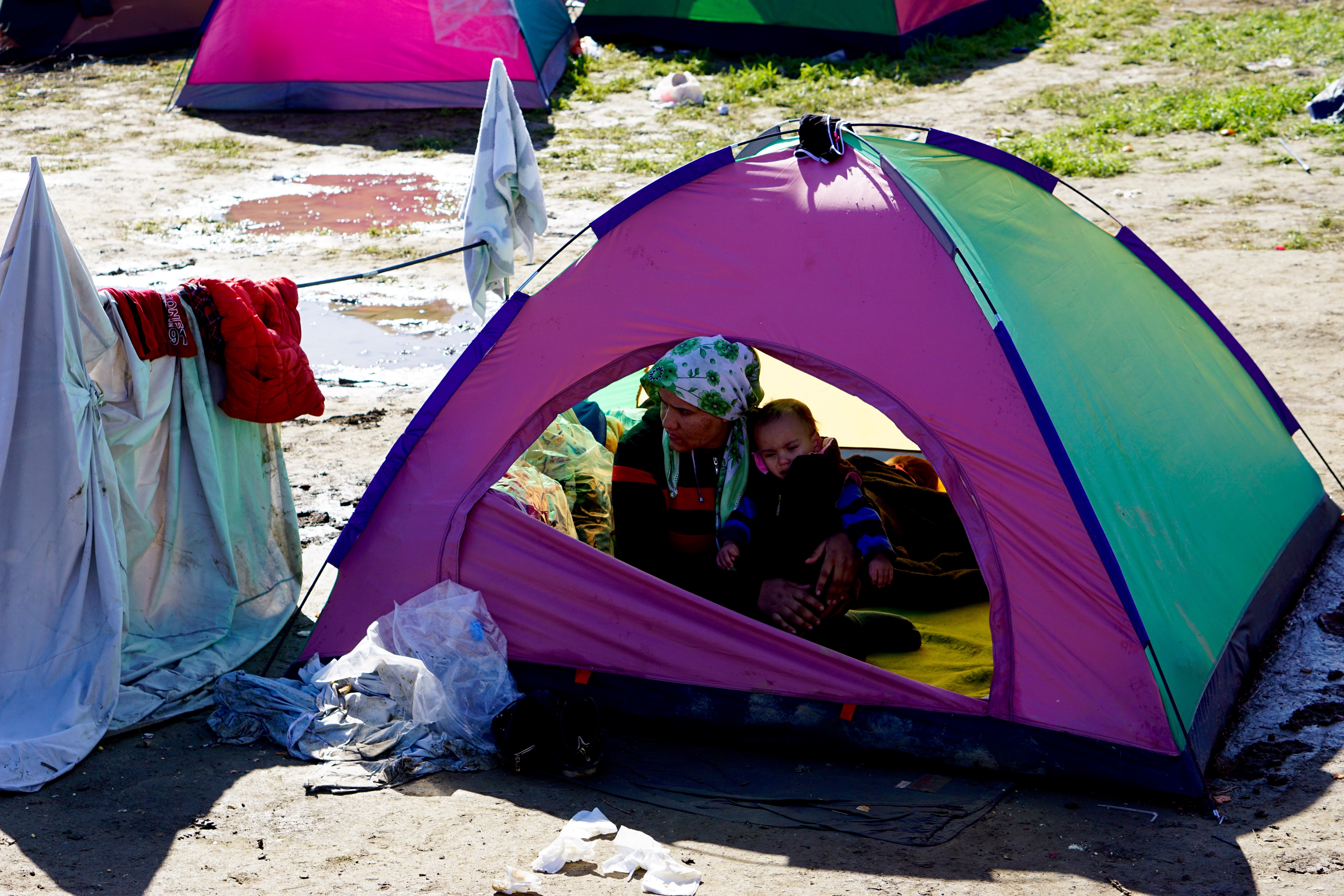 A woman and child huddle in a tent in a makeshift encampment in Idomeni, Greece, waiting for permission to move onto other points in Europe, March 4, 2016.