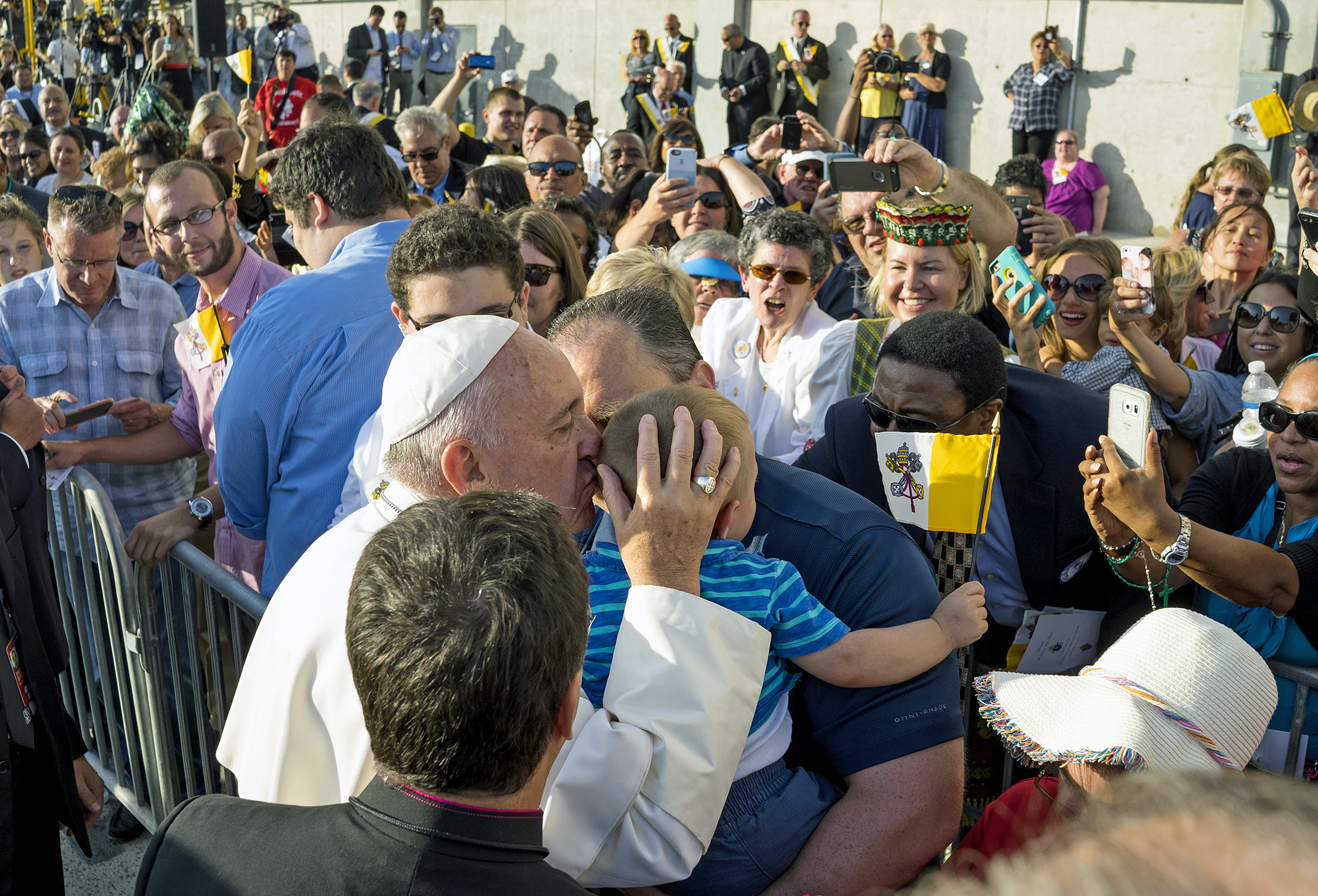 Pope Francis engages well wishes as he kisses a child after arriving at John F. Kennedy International Airport in New York,  Sept. 24, 2015.