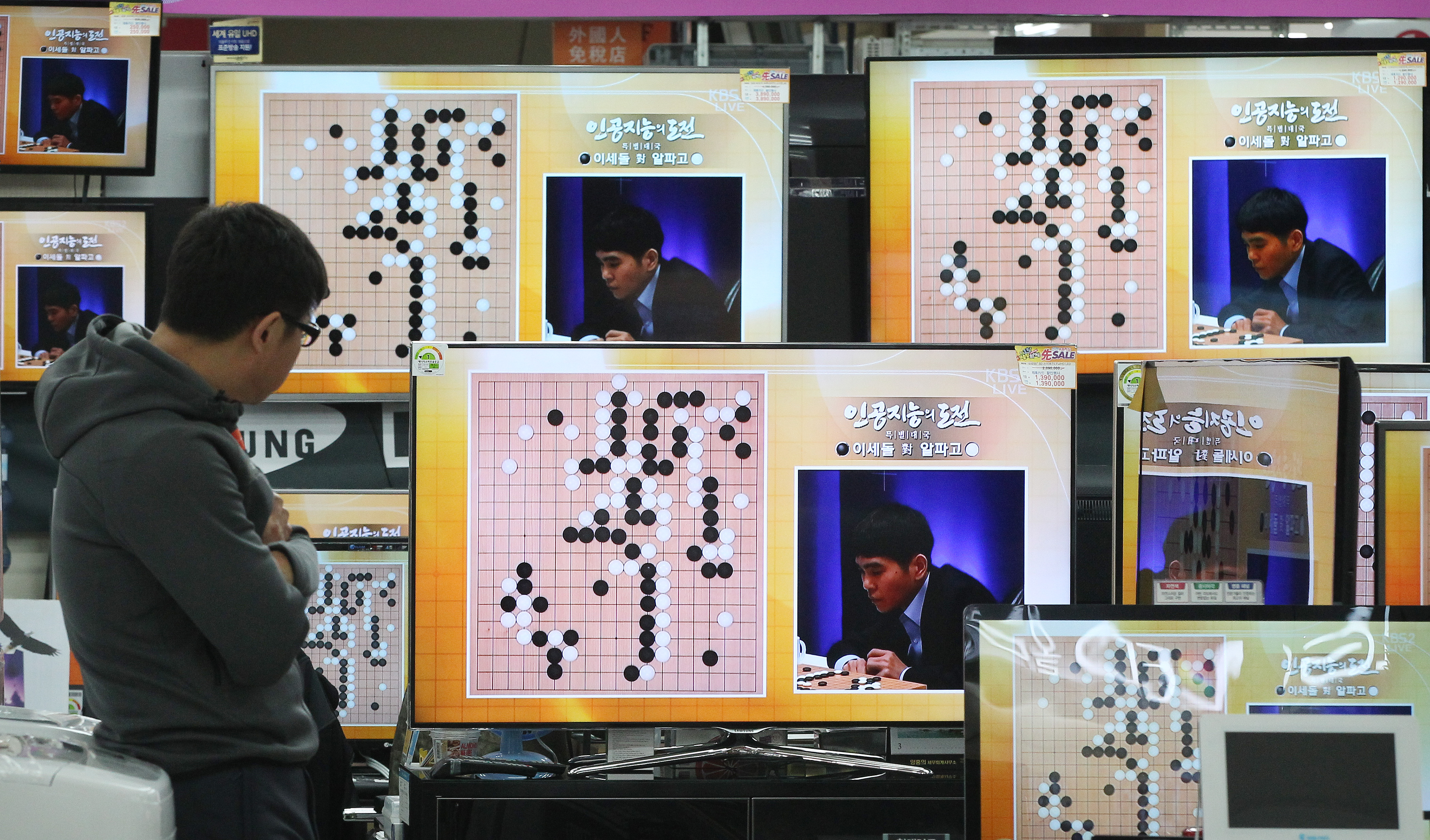 South Korean professional Go player Lee Sedol is seen on the TV screens in a matchup with Google's artificial intelligence program, AlphaGo, at the Yongsan Electronic store in Seoul, South Korea, March 9, 2016.