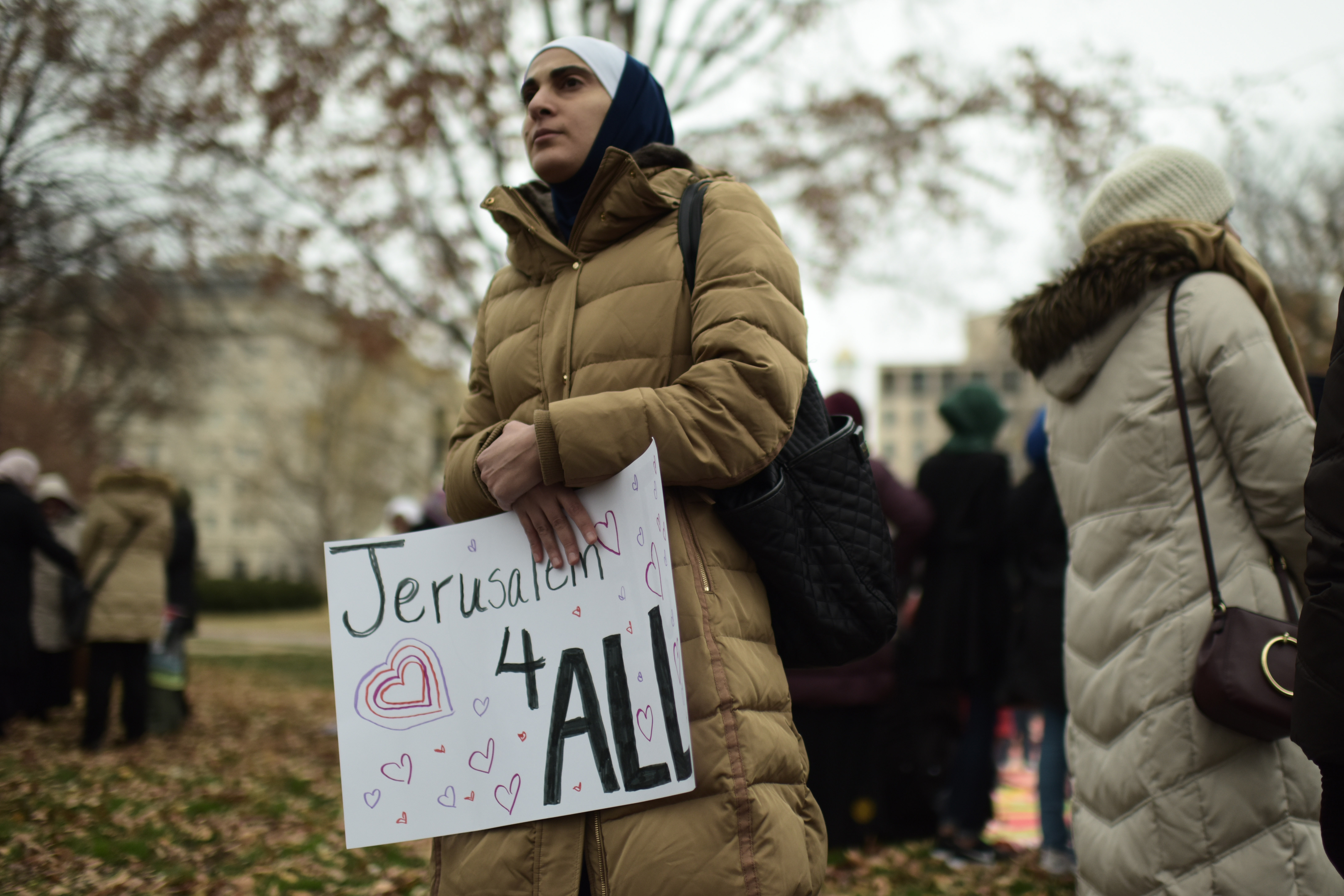 """A woman carries a poster reading """"Jerusalem for All"""" as Muslim worshippers gathered in front of the White House for Friday prayers in Washington D.C. to protest U.S. President Donald Trump's declaration of Jerusalem as Israel's capital, Dec. 08, 2017..."""