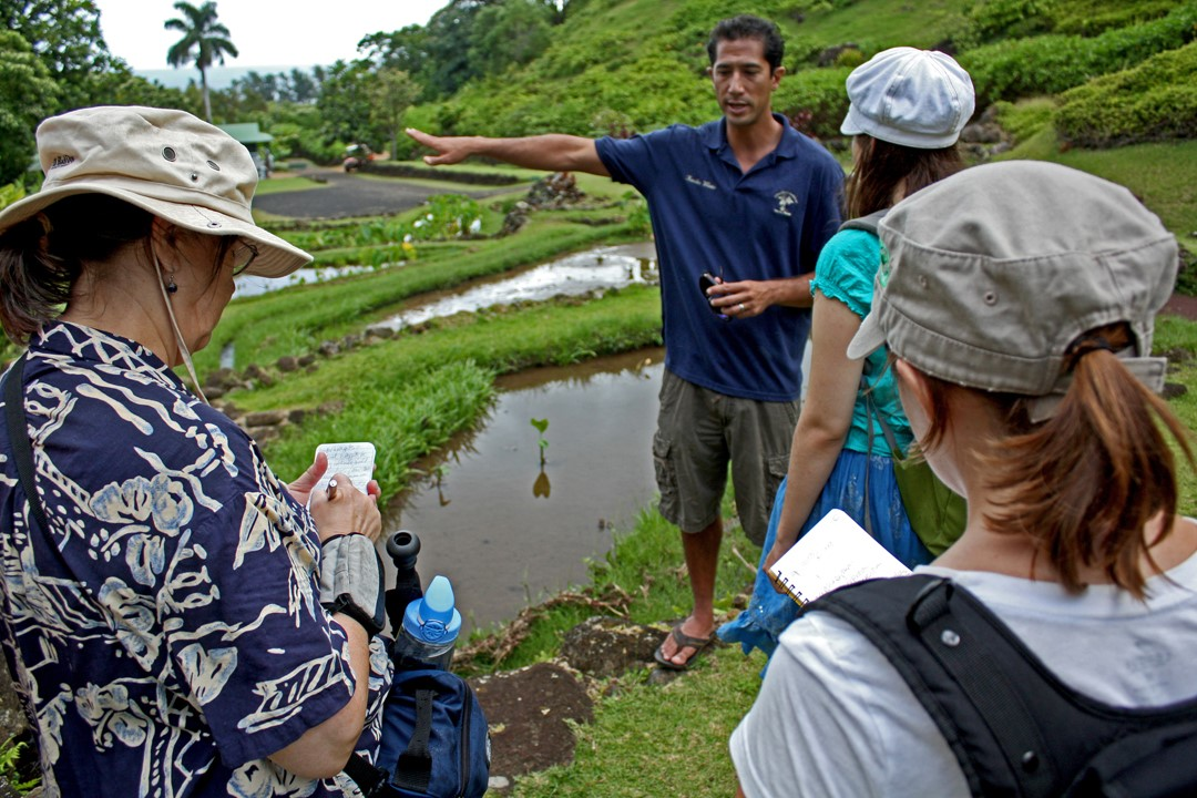 Kawika Winter gives a tour of the garden to a group of environmental journalists.