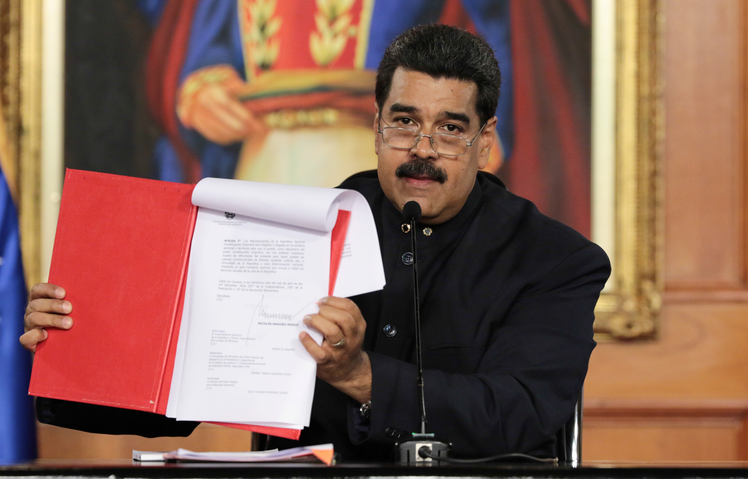 Venezuela's President Nicolas Maduro holds a document as he speaks during a ceremony at Miraflores Palace in Caracas, May 1, 2017.