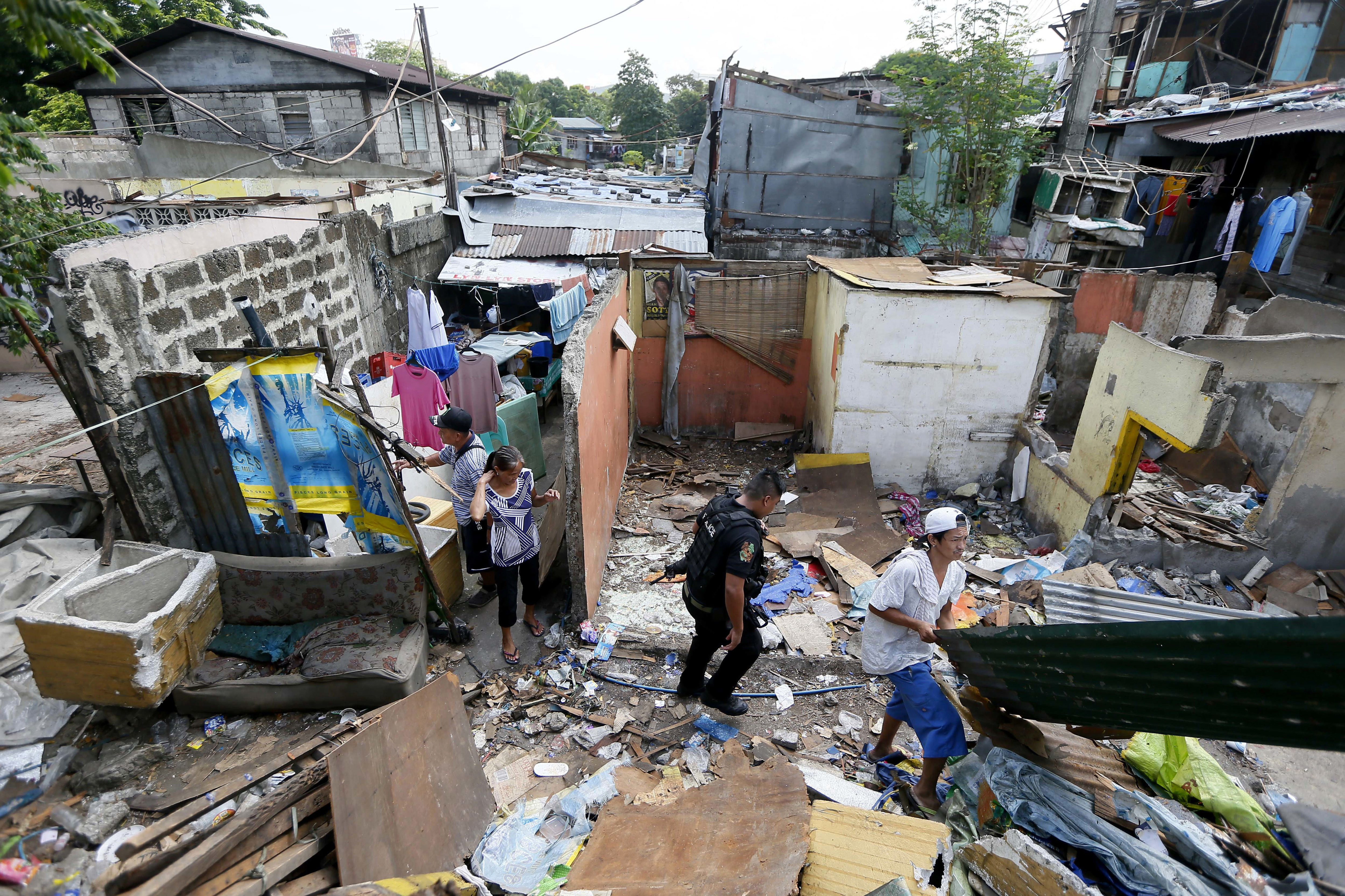 A member of the Philippine National Police SWAT team walks through debris as former inhabitants try to salvage any items following the demolition of their community Monday, June 6, 2016 in suburban Quezon city northeast of Manila, Philippines.