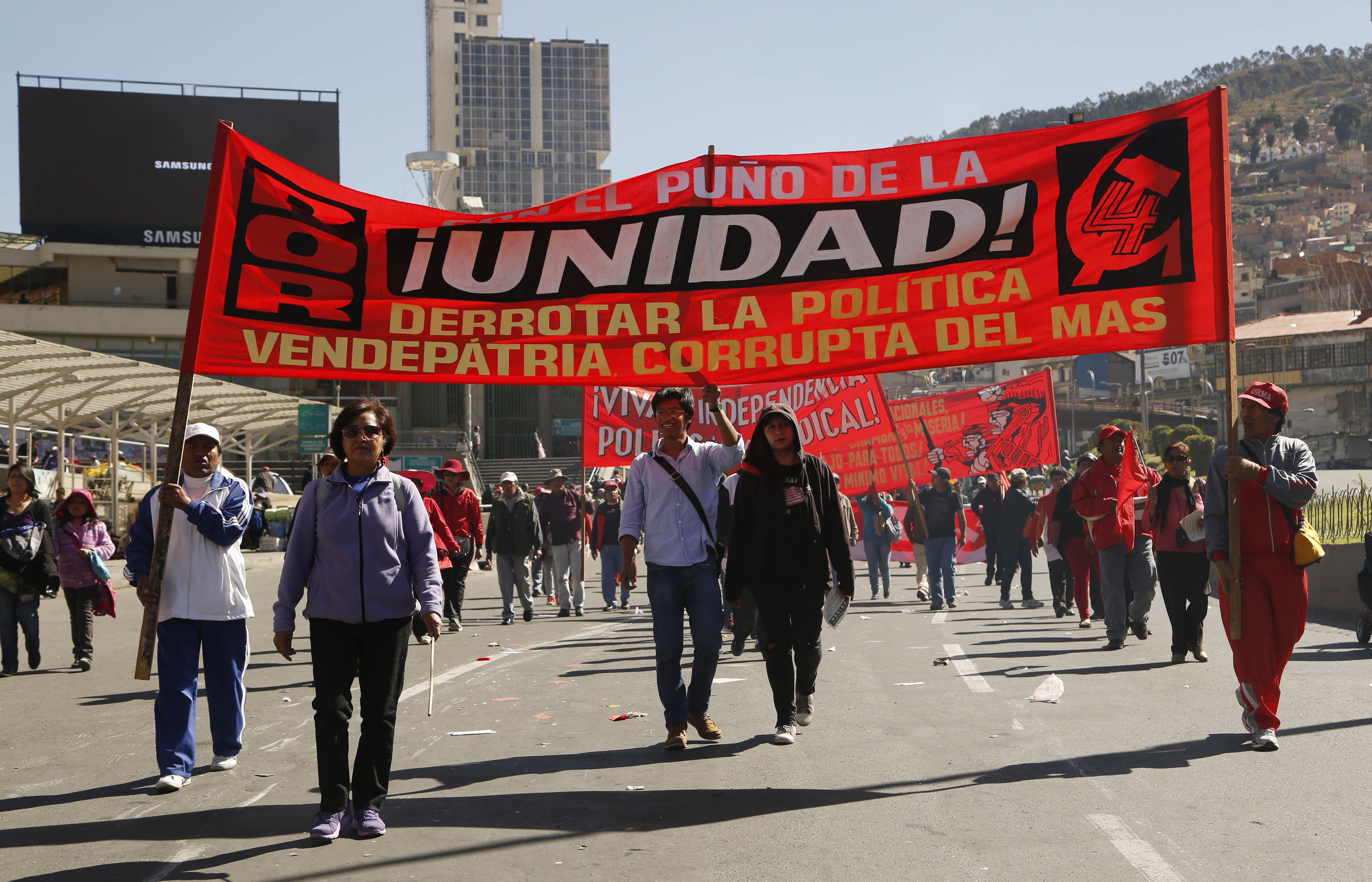 "Workers march in front of a banner with a message that reads in Spanish ""The fist of unity, defeating the traitorous policies of MAS (ruling party),"" during a May Day march, in La Paz, Bolivia, May 1, 2015."