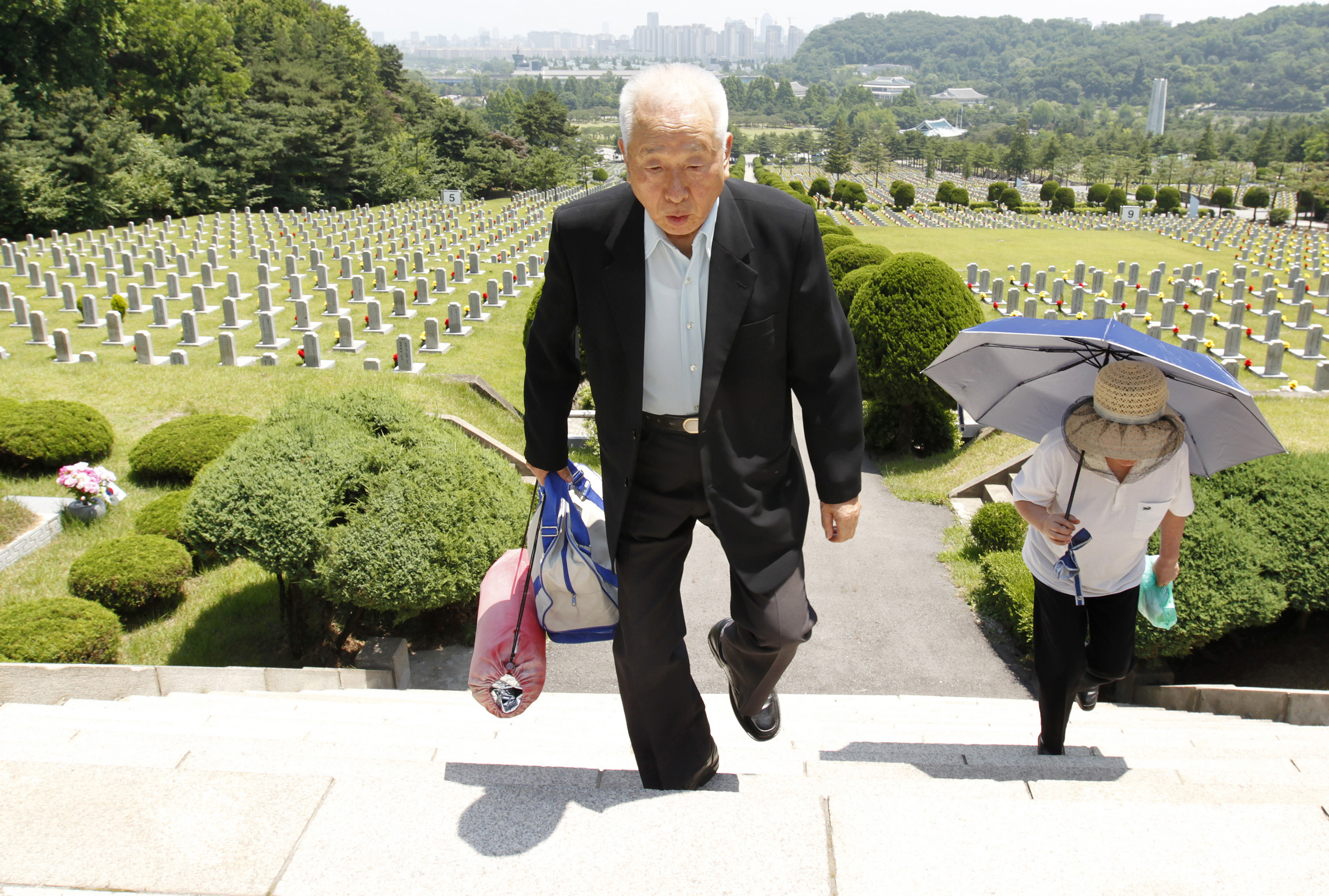 FILE - Ju Hong-jang, left, 81, and his wife Yoon Bok-hee, 73, leave after they visited a gravestone of his father Ju Bong-gyeom, a police officer who died in 1952 during the Korean War, at the National Cemetery in Seoul, June 23, 2010. Ju's father to...