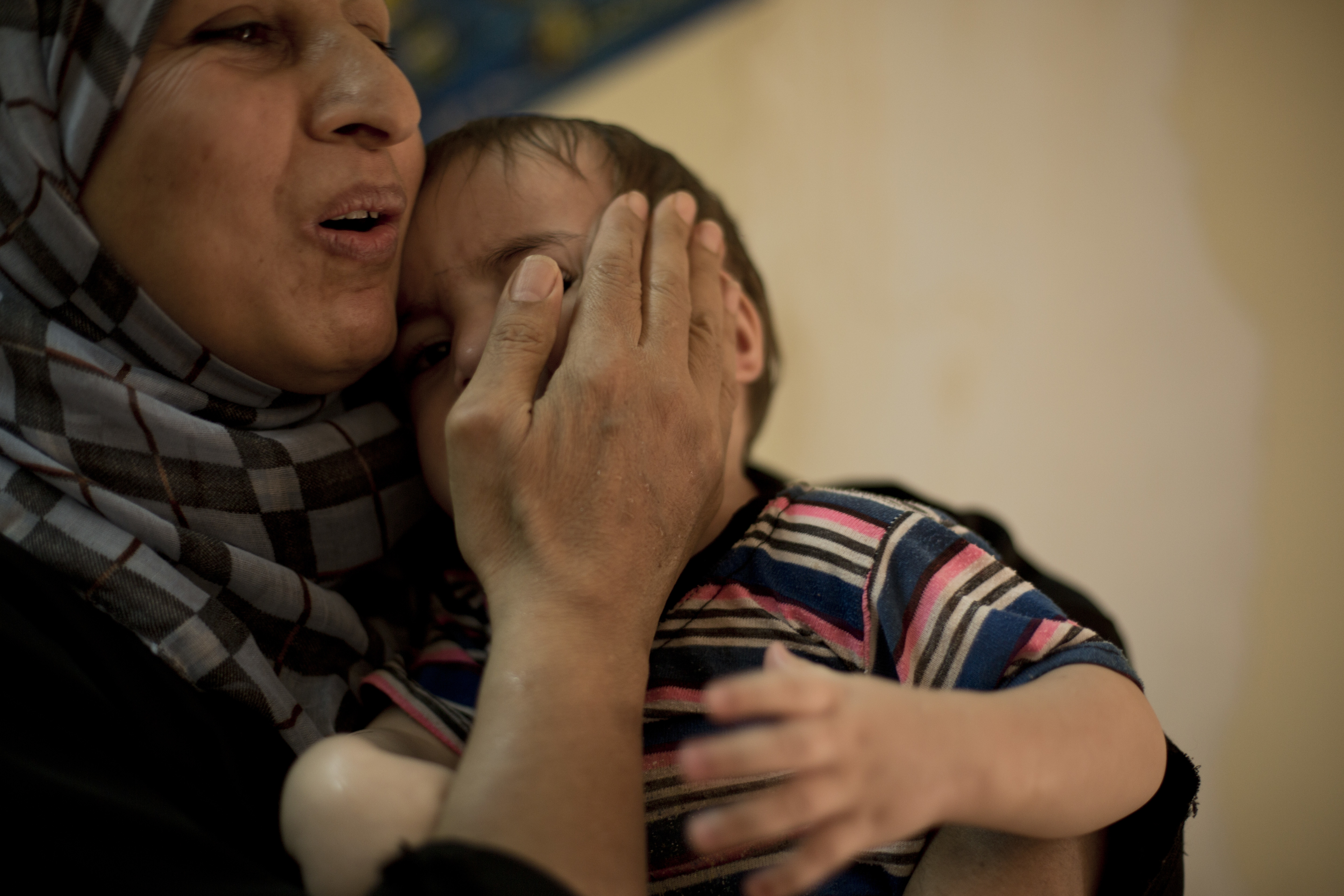 FILE - A worker comforts a toddler at Salhiya Orphanage, which now hosts foreign and Iraqi children of Islamic State militants, in Baghdad, Iraq, Aug. 16, 2018. The war to drive out IS militants left tens of thousands of orphans.