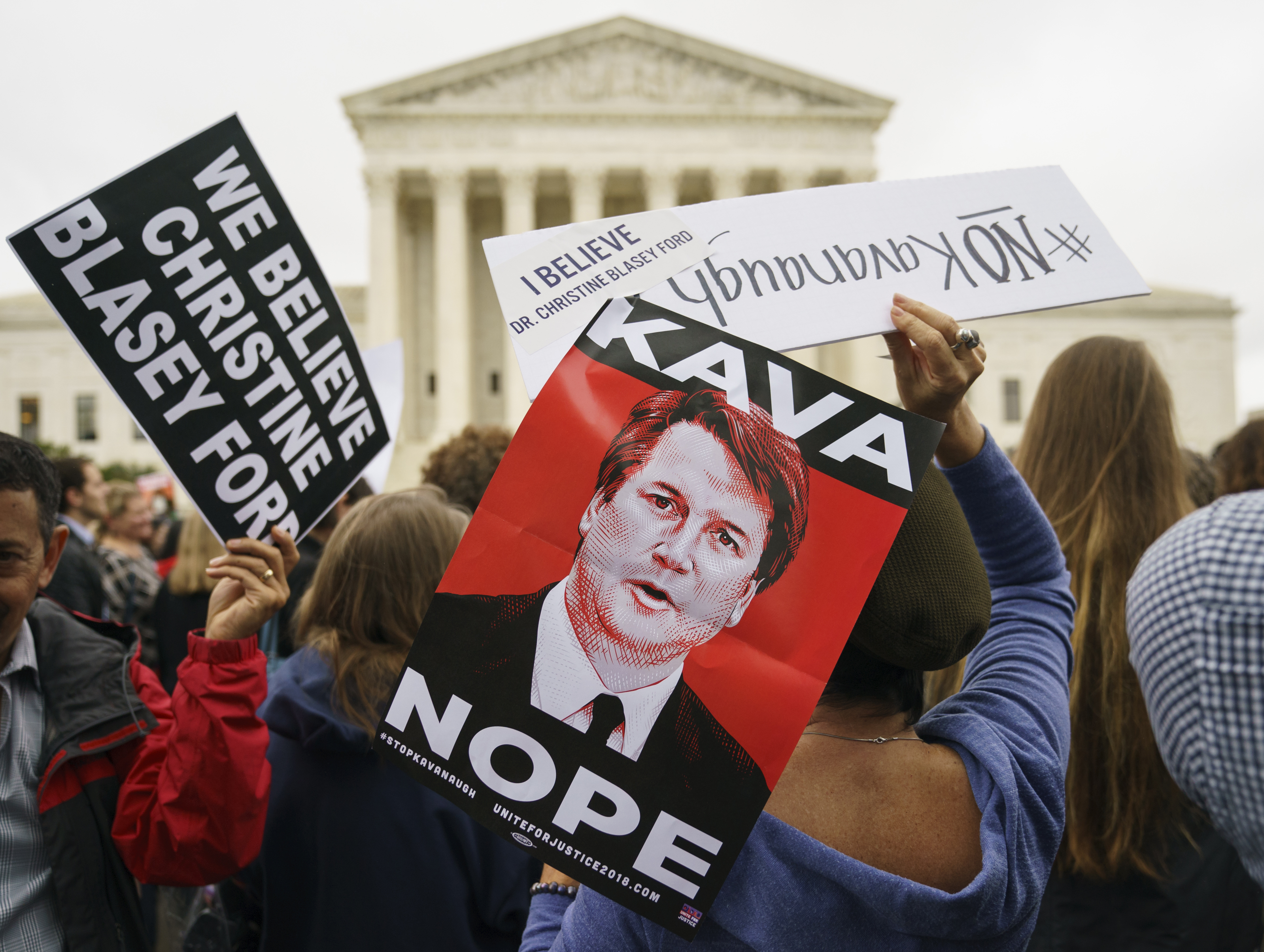 "Protesters in front of the Supreme Court hold signs with an image of Judge Brett Kavanaugh that reads ""Kava Nope"" and ""We Believe Christine Blasey Ford"" in Washington, Sept. 24, 2018."