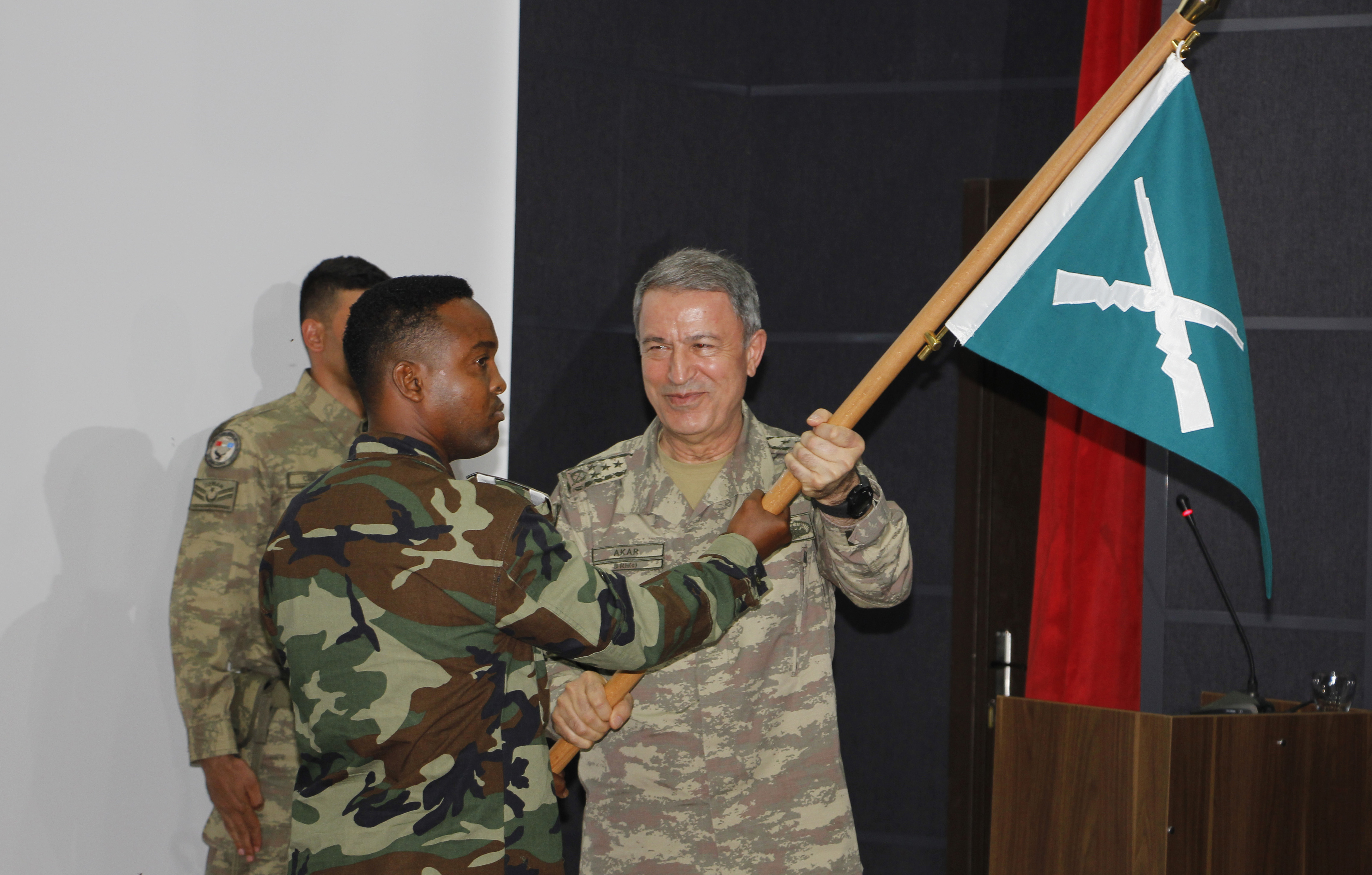 Turkish Chief of Staff General Hulusi Akar, right, hands a flag to a Somali soldier at the new Turkey-Somali military training center in  Mogadishu, Sept. 30, 2017.
