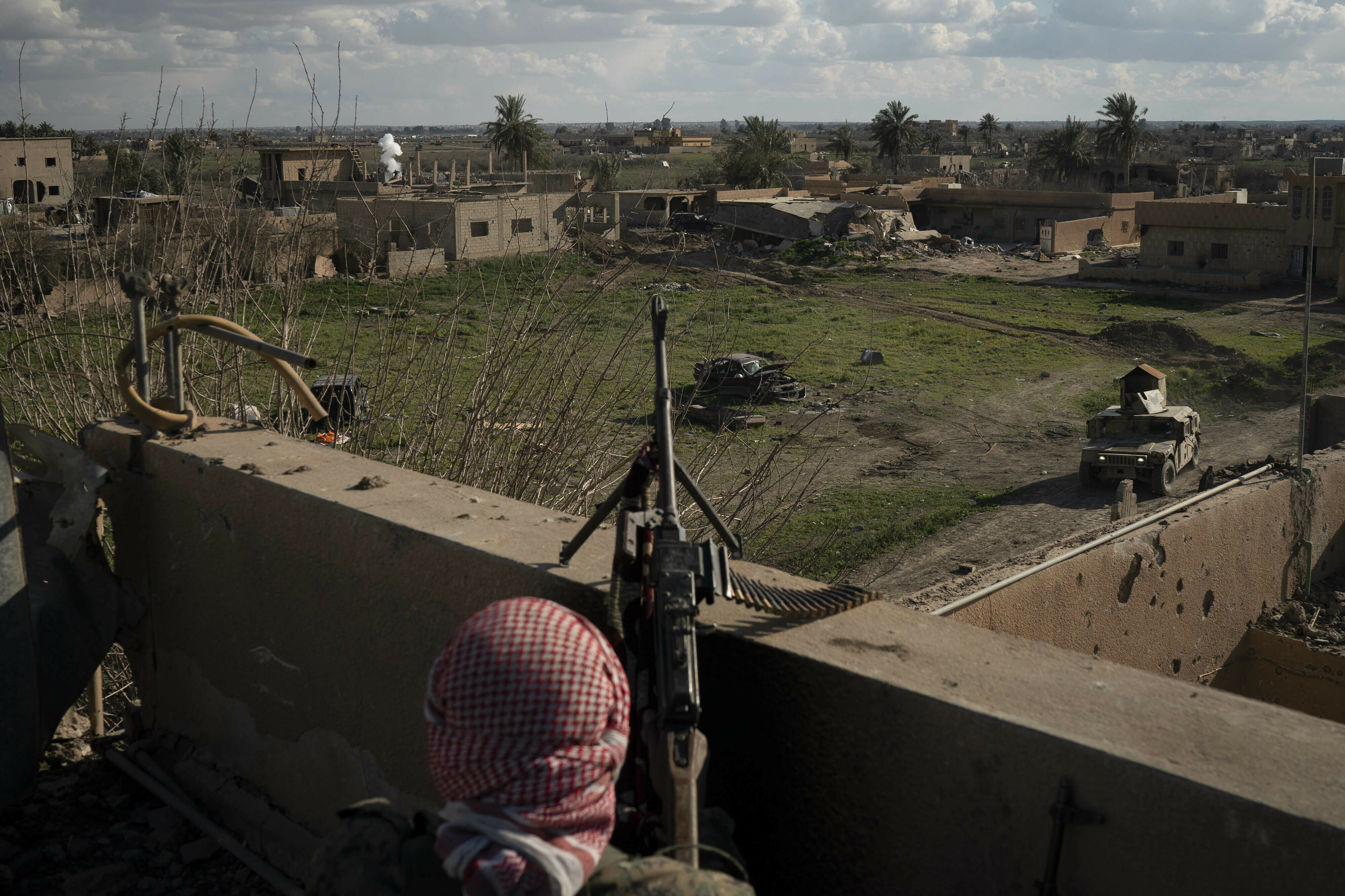 A U.S.-backed Syrian Democratic Forces fighter stands atop a building used as a temporary base near the last land still held by Islamic State militants in Baghouz, Syria, Feb. 18, 2019.
