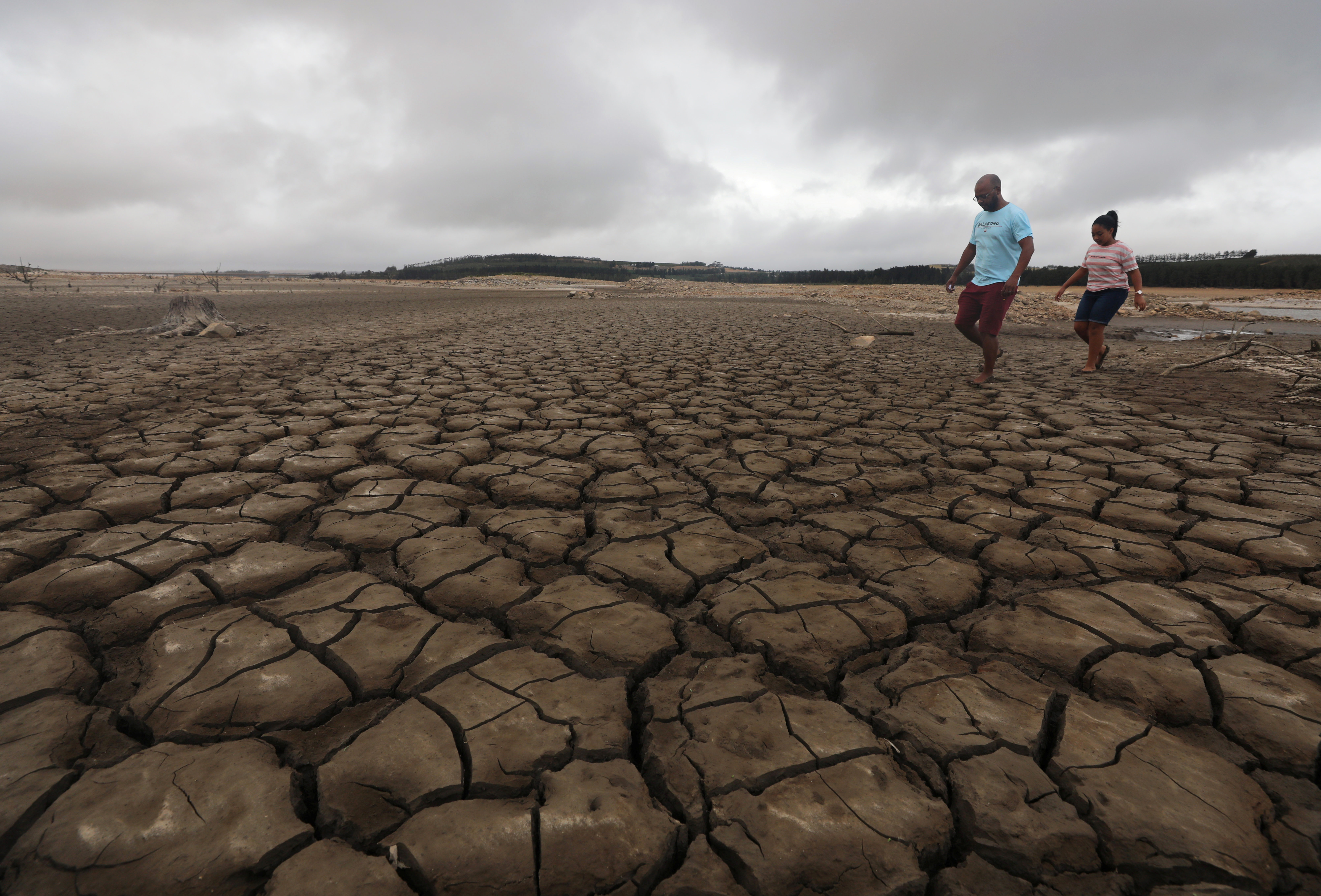 A family negotiates their way through caked mud around a dried up section of the Theewaterskloof dam near Cape Town, South Africa, Jan. 20, 2018.