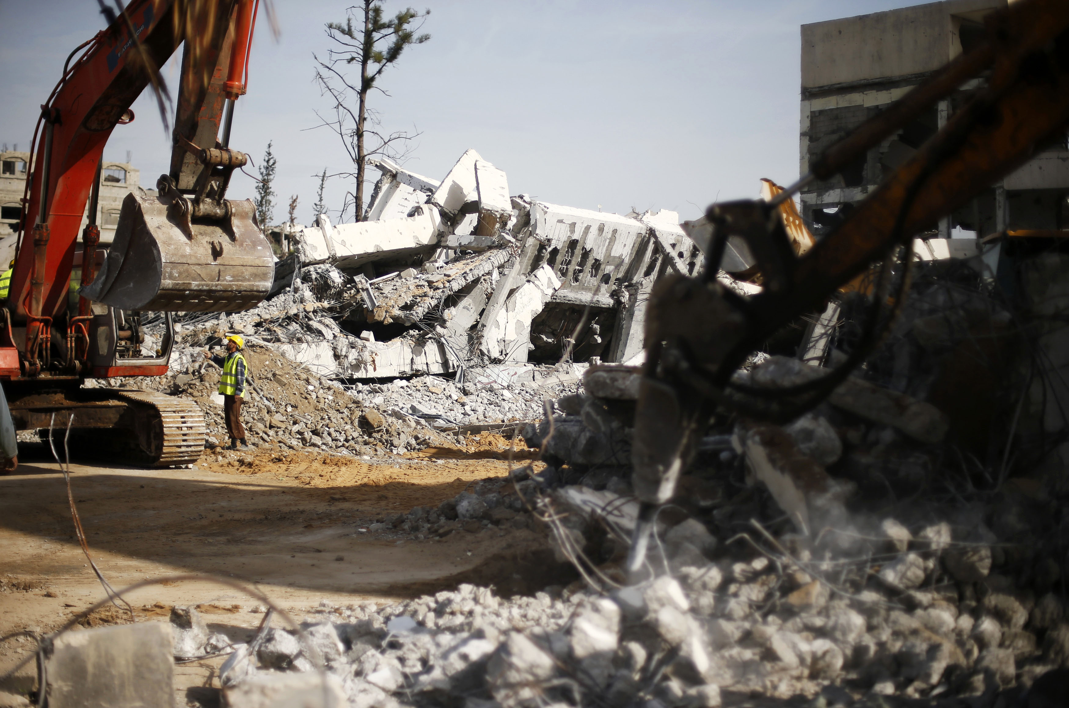 Palestinian workers clear the rubble of a school that witnesses said was destroyed by Israeli shelling during the most recent conflict between Israel and Hamas, in the east of Gaza City, Dec. 3, 2014.