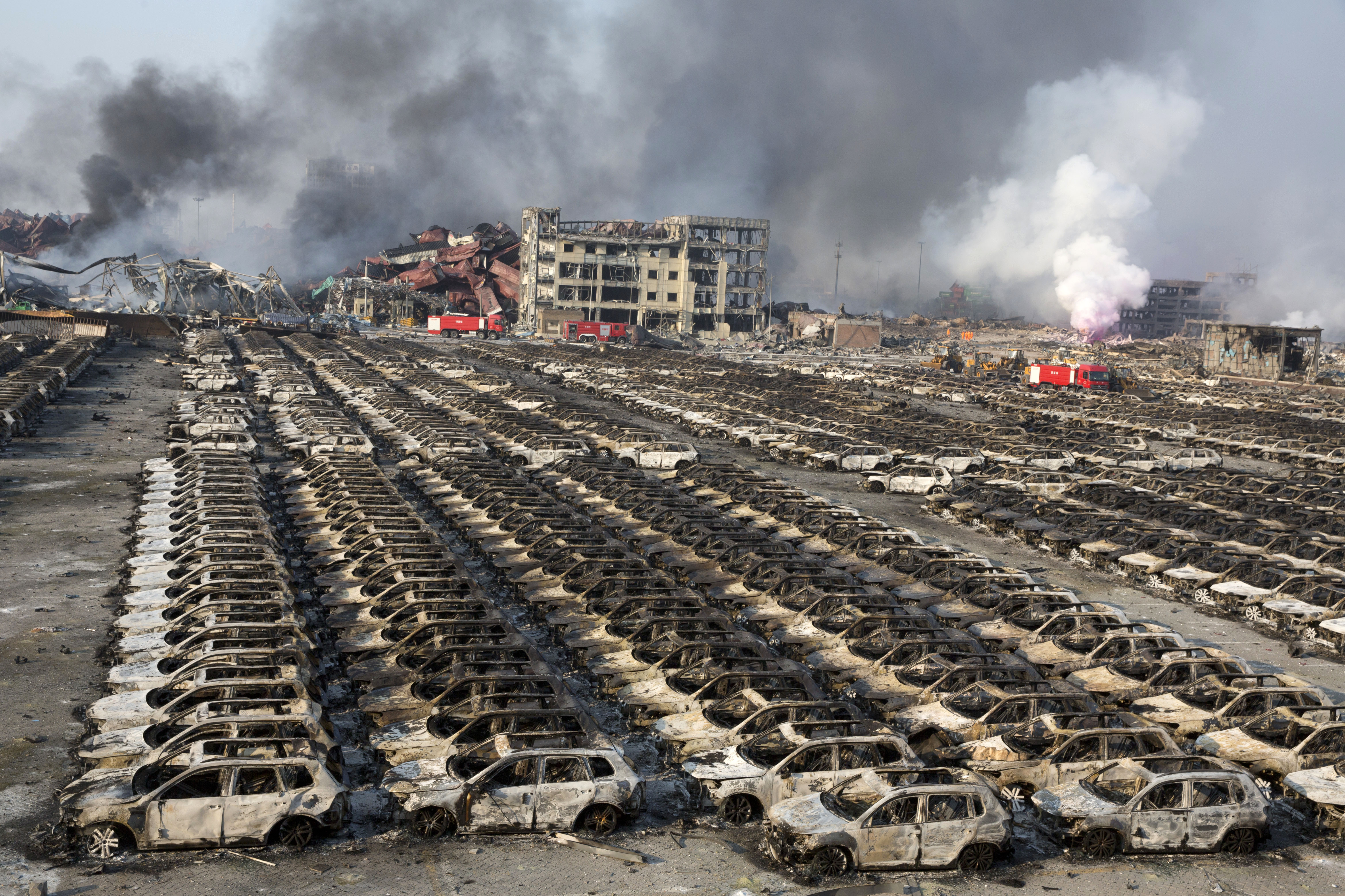 Smoke billows out from the site of an explosion that reduced a parking lot filled with new cars to charred remains at a warehouse in northeastern China's Tianjin municipality, Aug. 13, 2015.