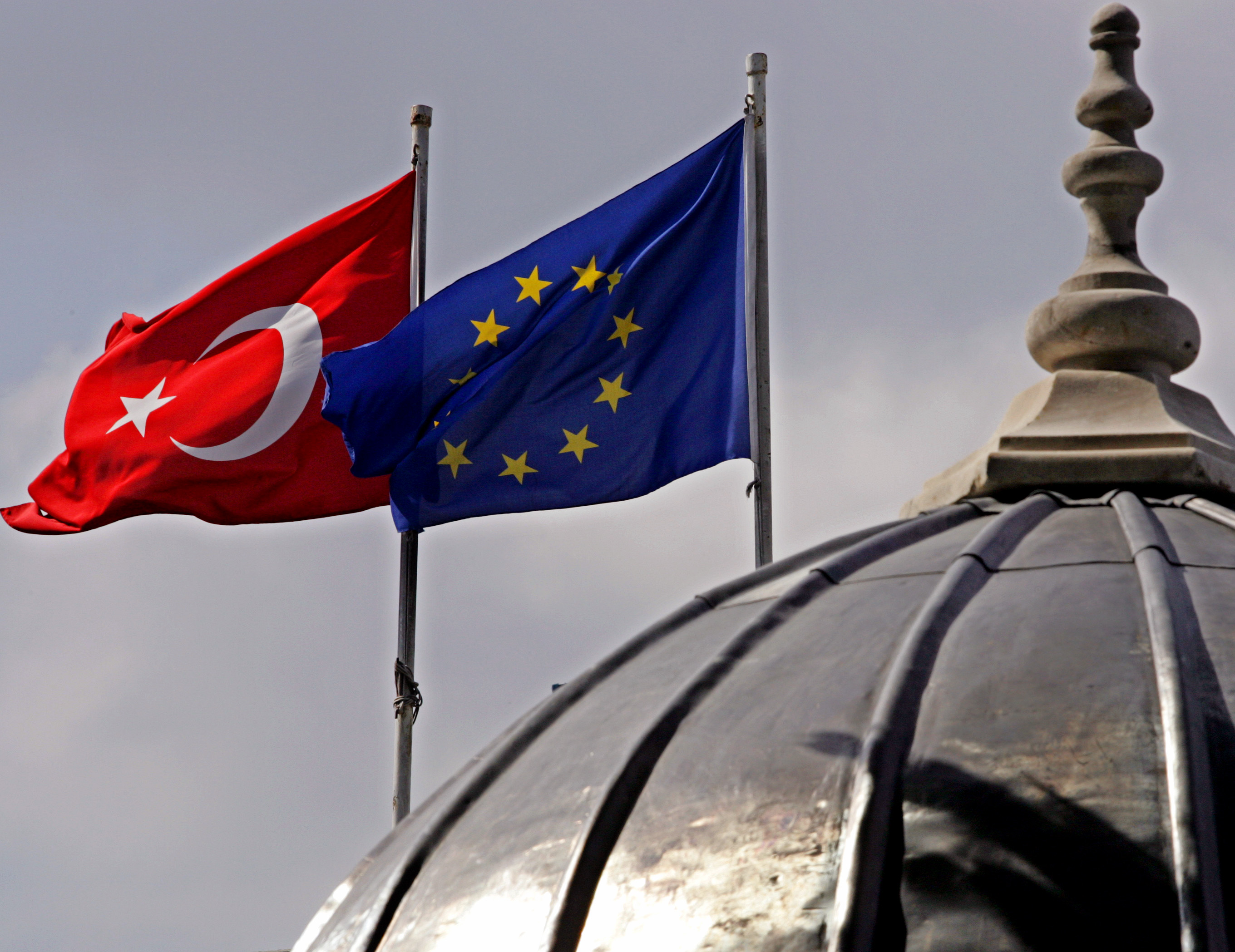FILE - Flags of Turkey and the European Union are seen over the dome of a mosque in Istanbul, Turkey, Oct. 4, 2005.