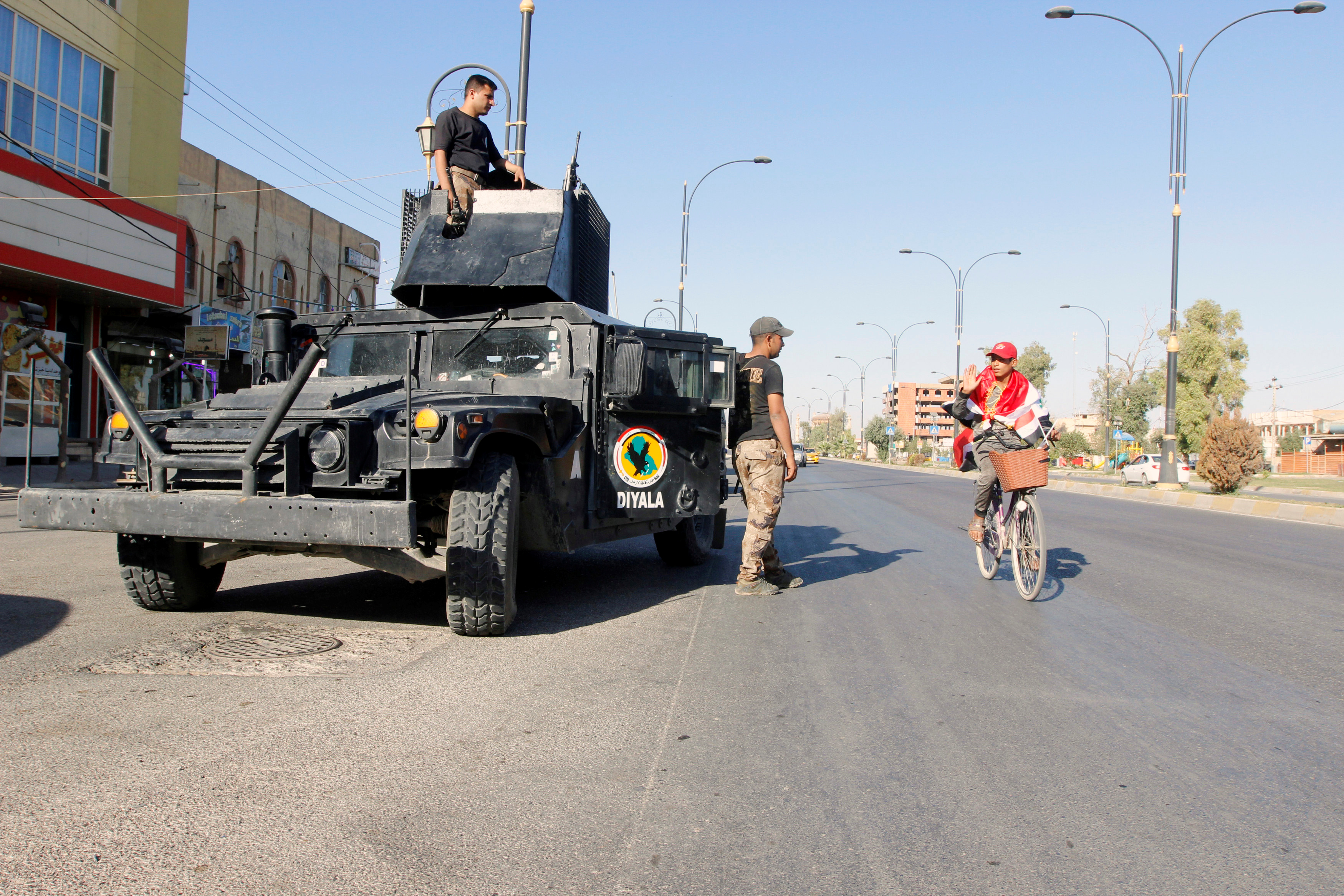 A cyclist gestures at Iraqi security forces, on a street of Kirkuk, Iraq, Oct. 19, 2017.