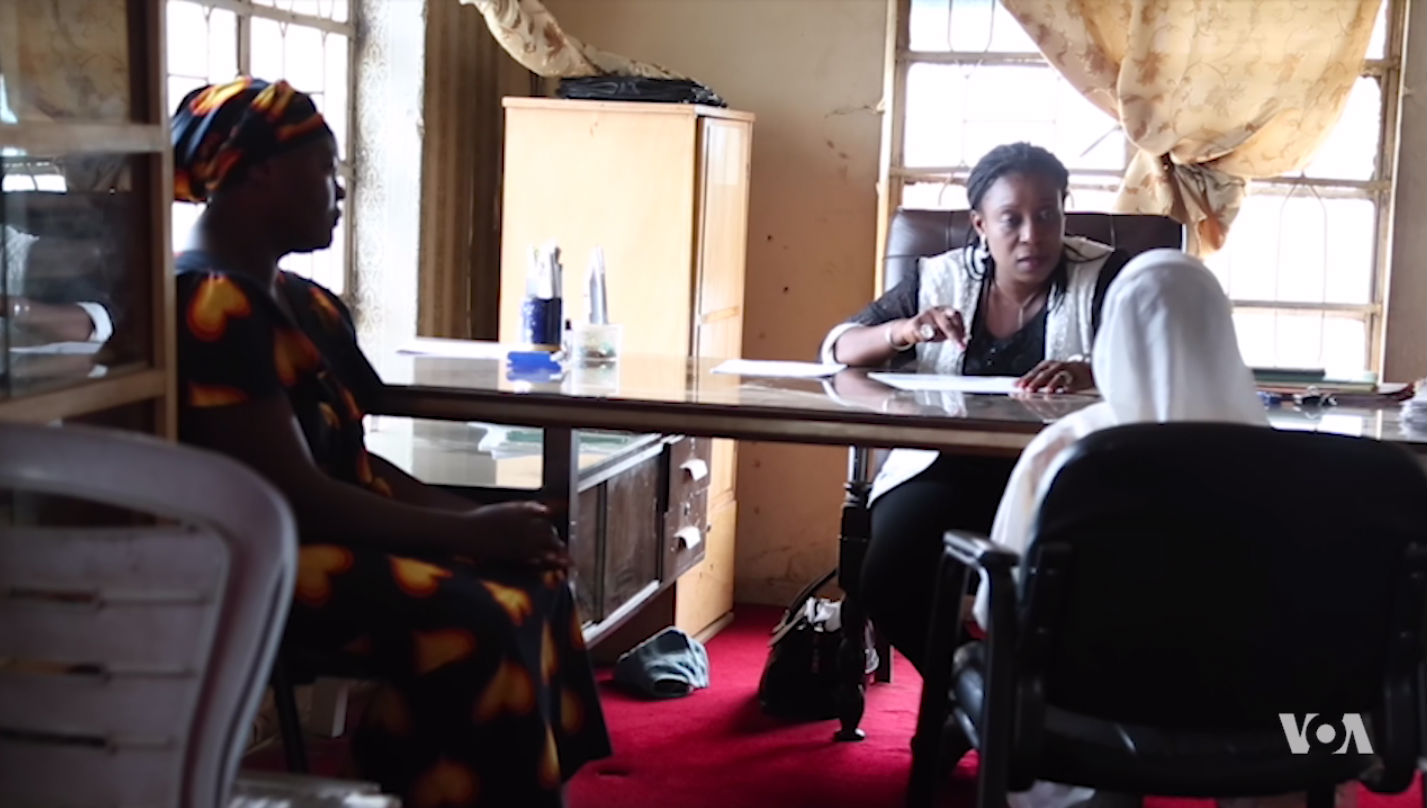 Mercy Philip (left) with her 8-year-old daughter (right in white) meet with a lawyer in northern Nigeria.