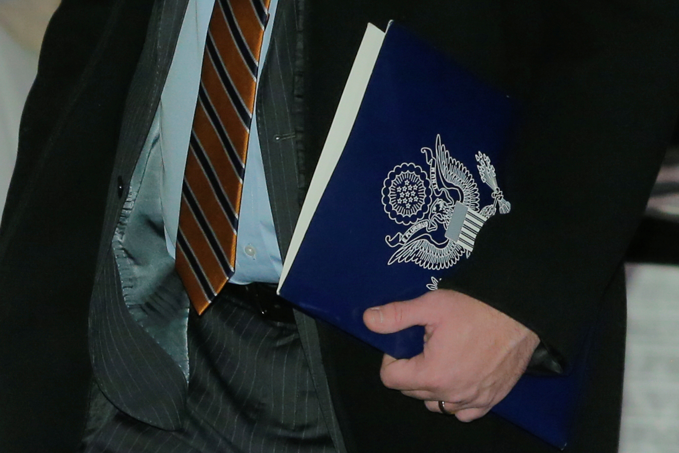 A member of the U.S. trade delegation to China, carries a folder as he leaves a hotel in Beijing, China January 7, 2019.