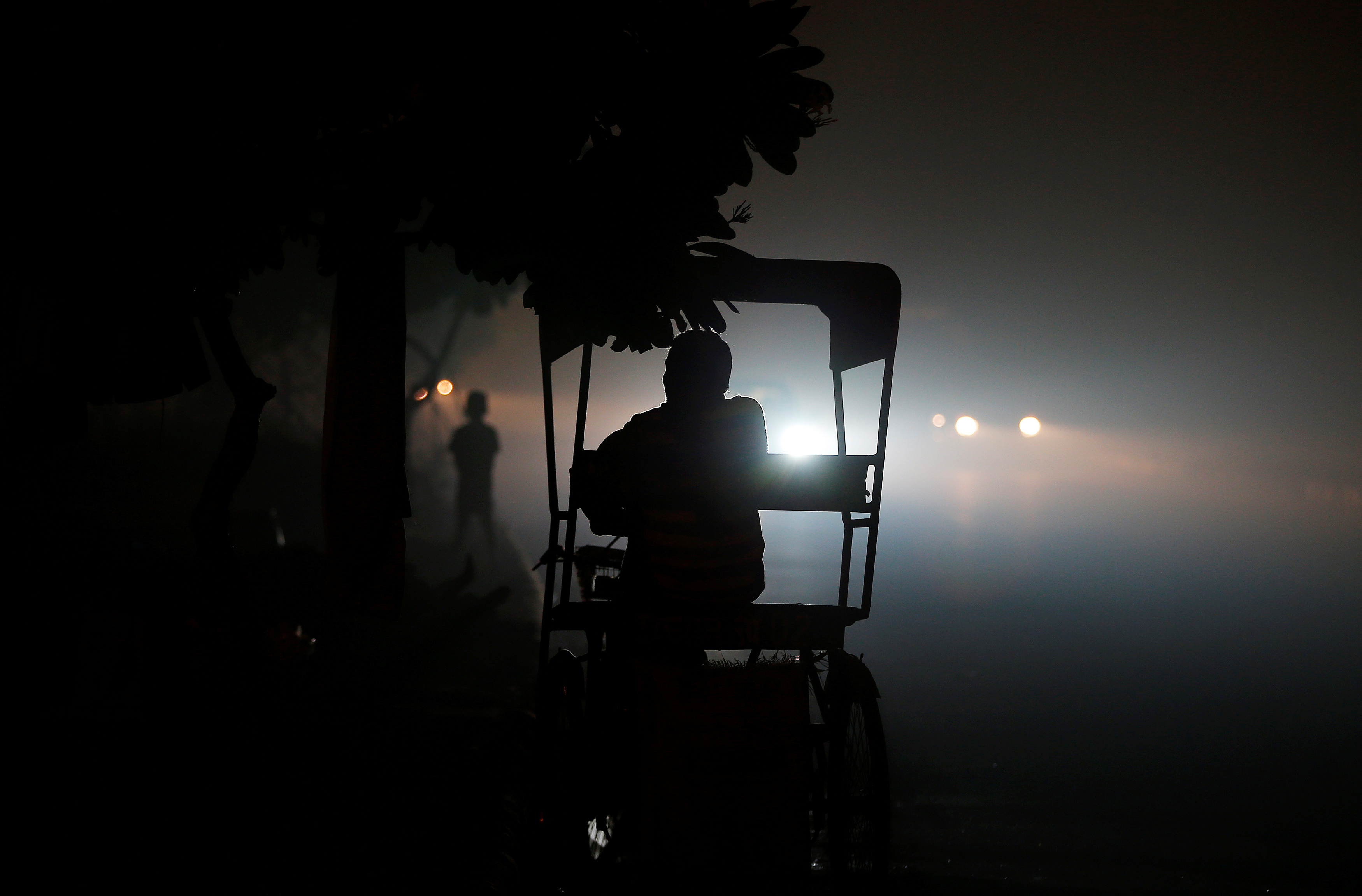 FILE - A rickshaw puller waits for customers along a roadside amidst heavy smog in New Delhi, India, Nov. 6, 2016.