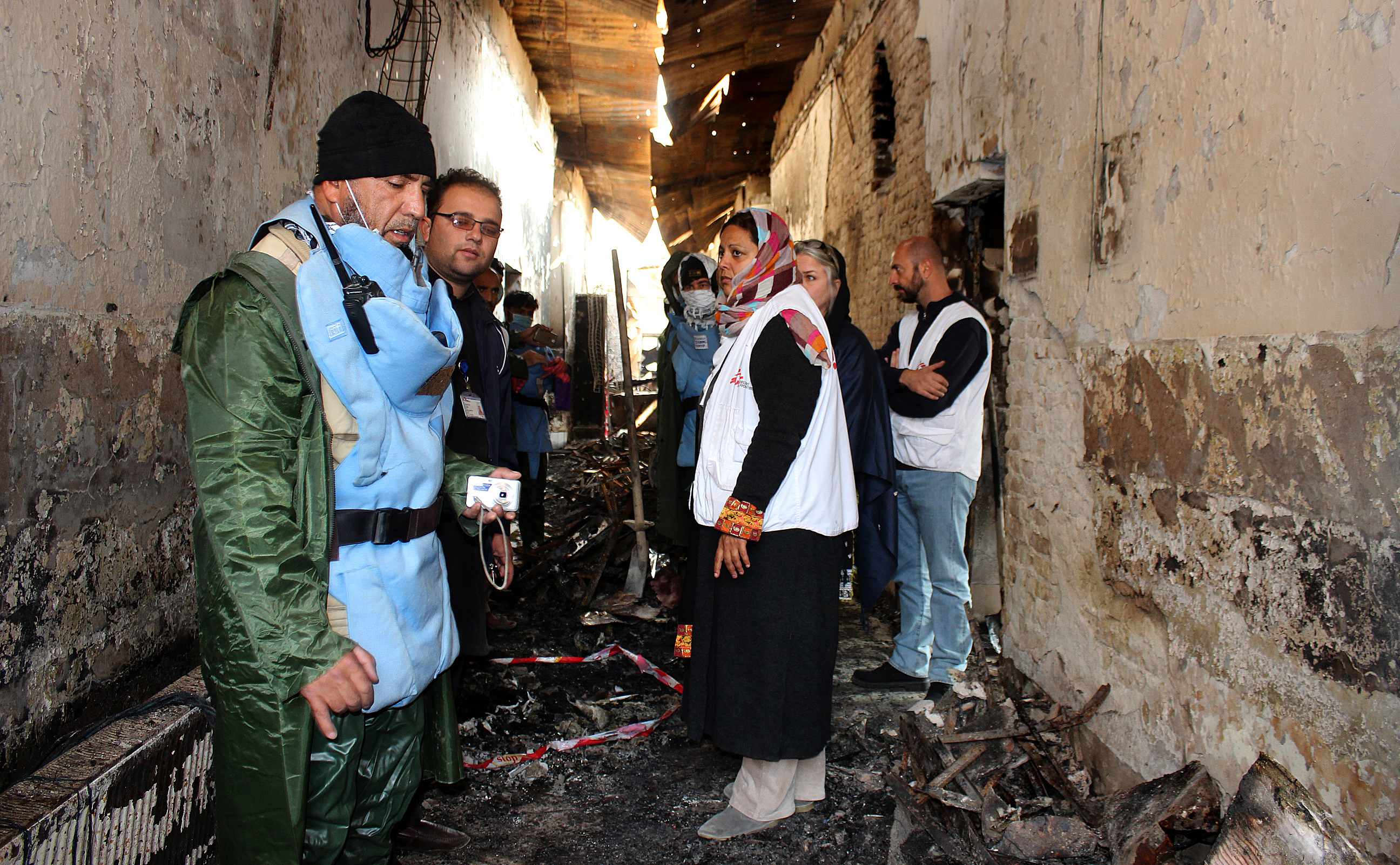 FILE - Afghan (L) talks to staff members in a charred corridor of the damaged Medecins Sans Frontieres (MSF) hospital in northern Kunduz.