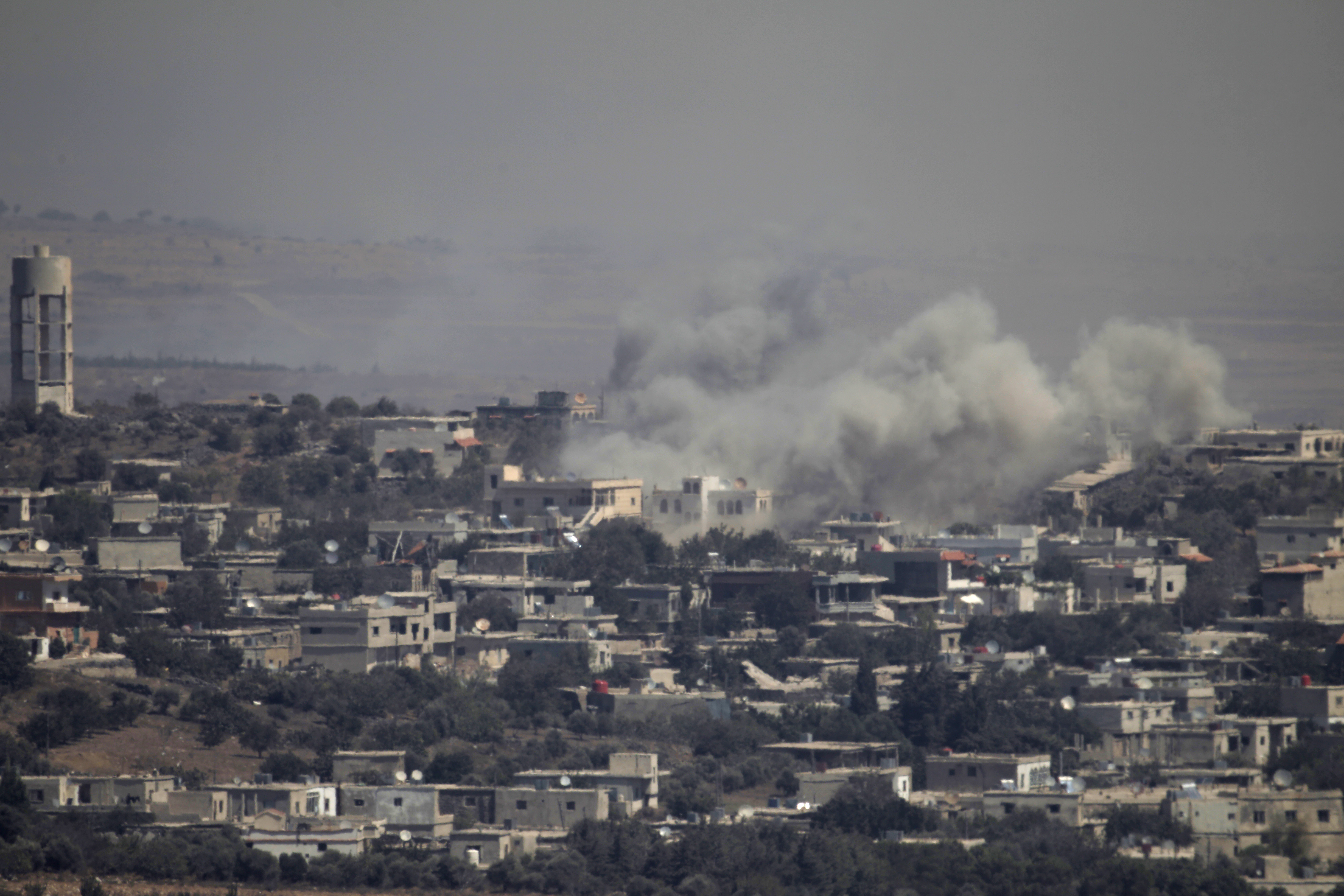 A picture taken from the Israeli-annexed Golan Heights shows smoke rising from the Syrian village of Jubata al-Khashab, Sept. 10, 2016. Israeli aircraft struck Syrian army positions Sept. 10 after fire from war-torn Syria hit the  Israeli-held zone o...