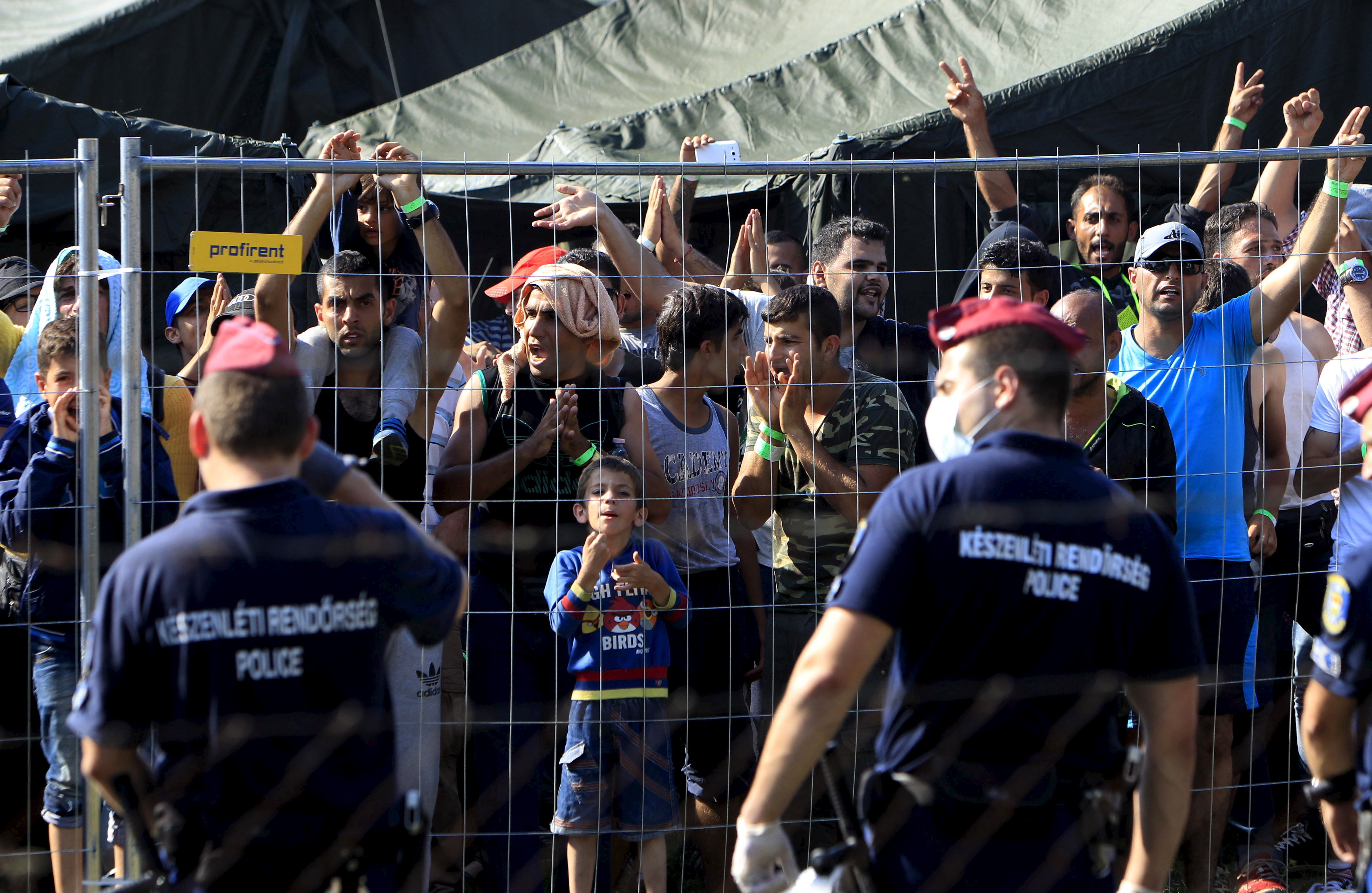 Syrian migrants shout slogans at a refugee camp in Roszke, Hungary, Aug. 28, 2015.
