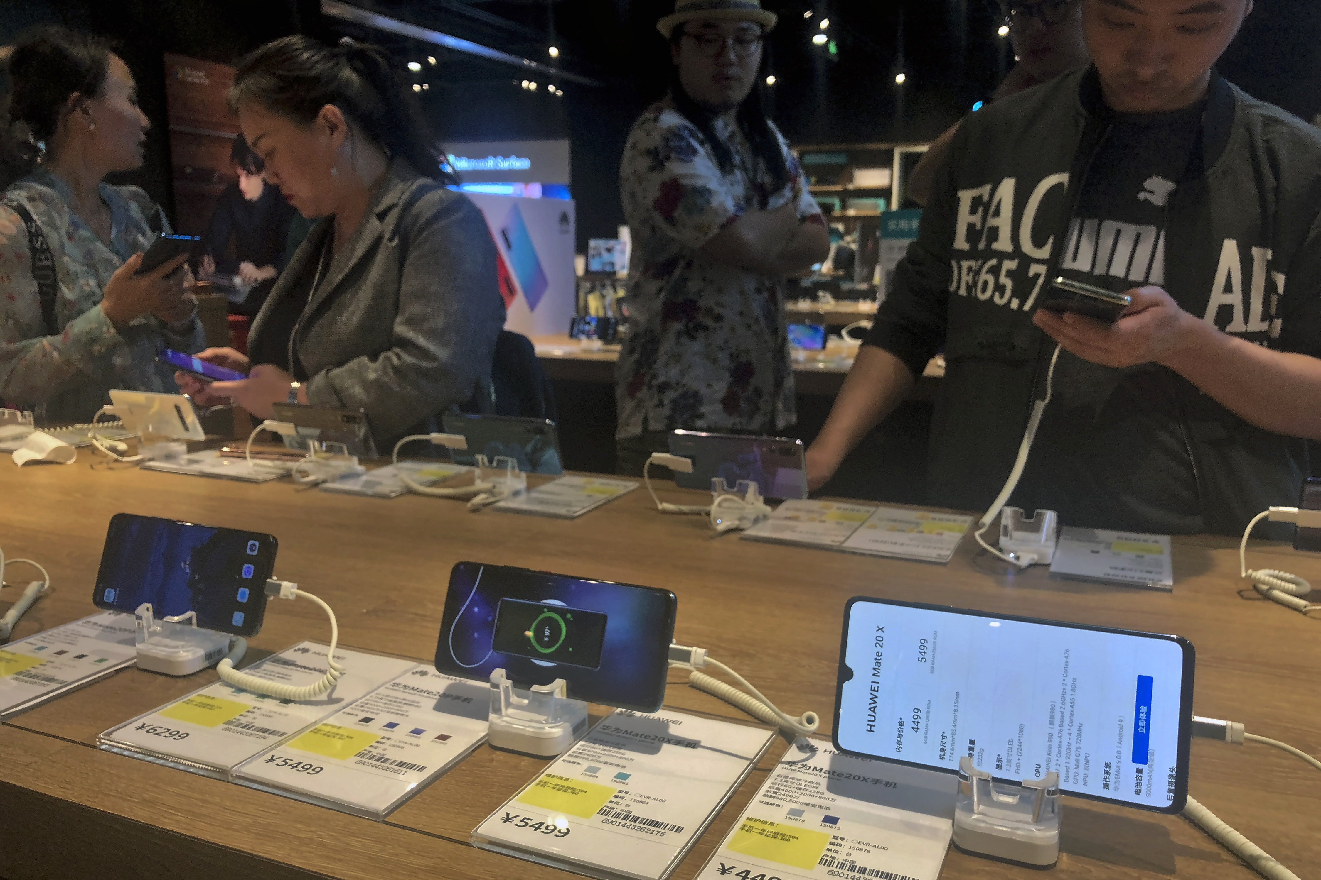 People try out Huawei smartphone models on display at an electronic store in Beijing, May 20, 2019.