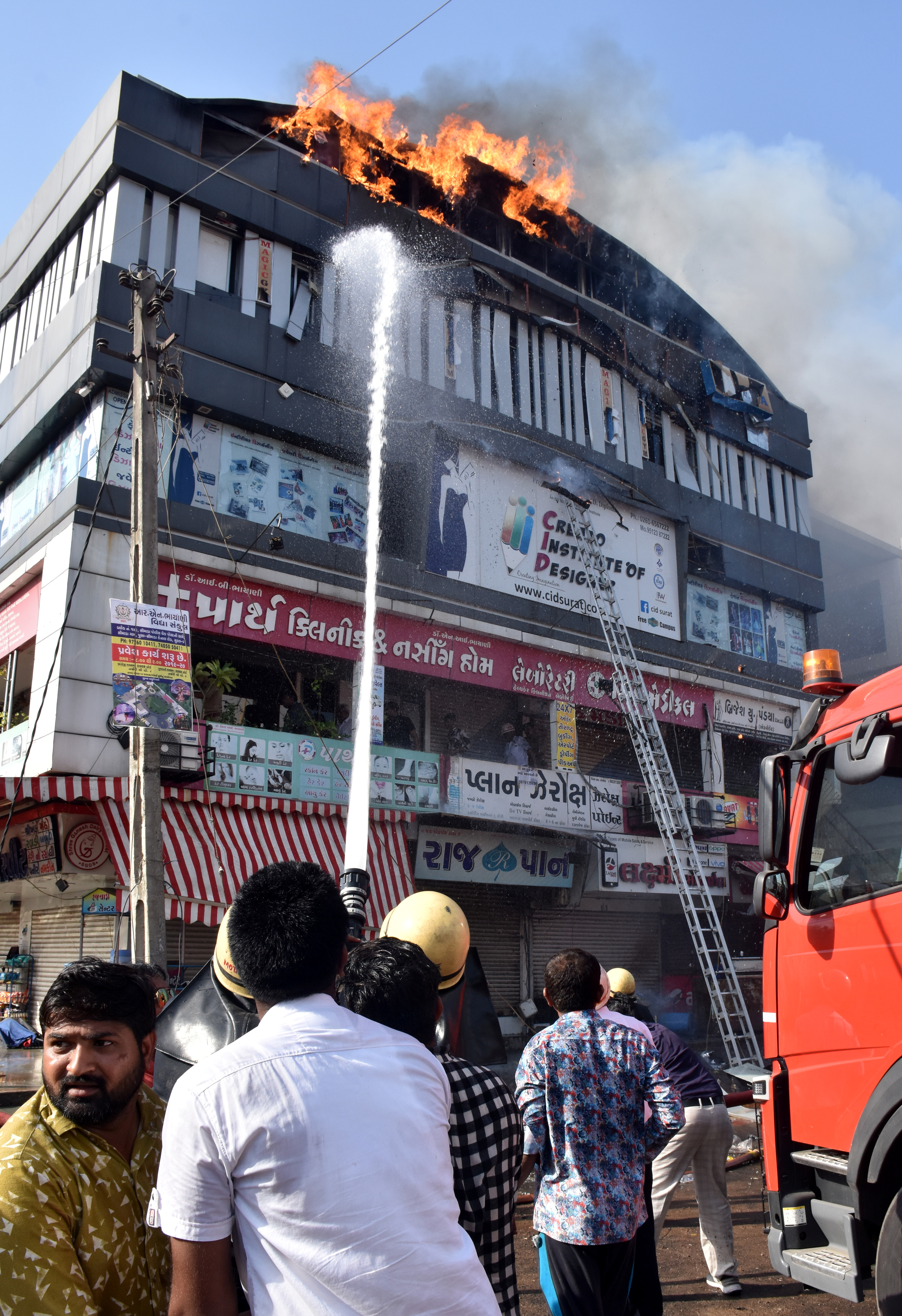 Firefighters douse a fire that broke out in a four-story commercial building in Surat, in the western state of Gujarat, India, May 24, 2019.