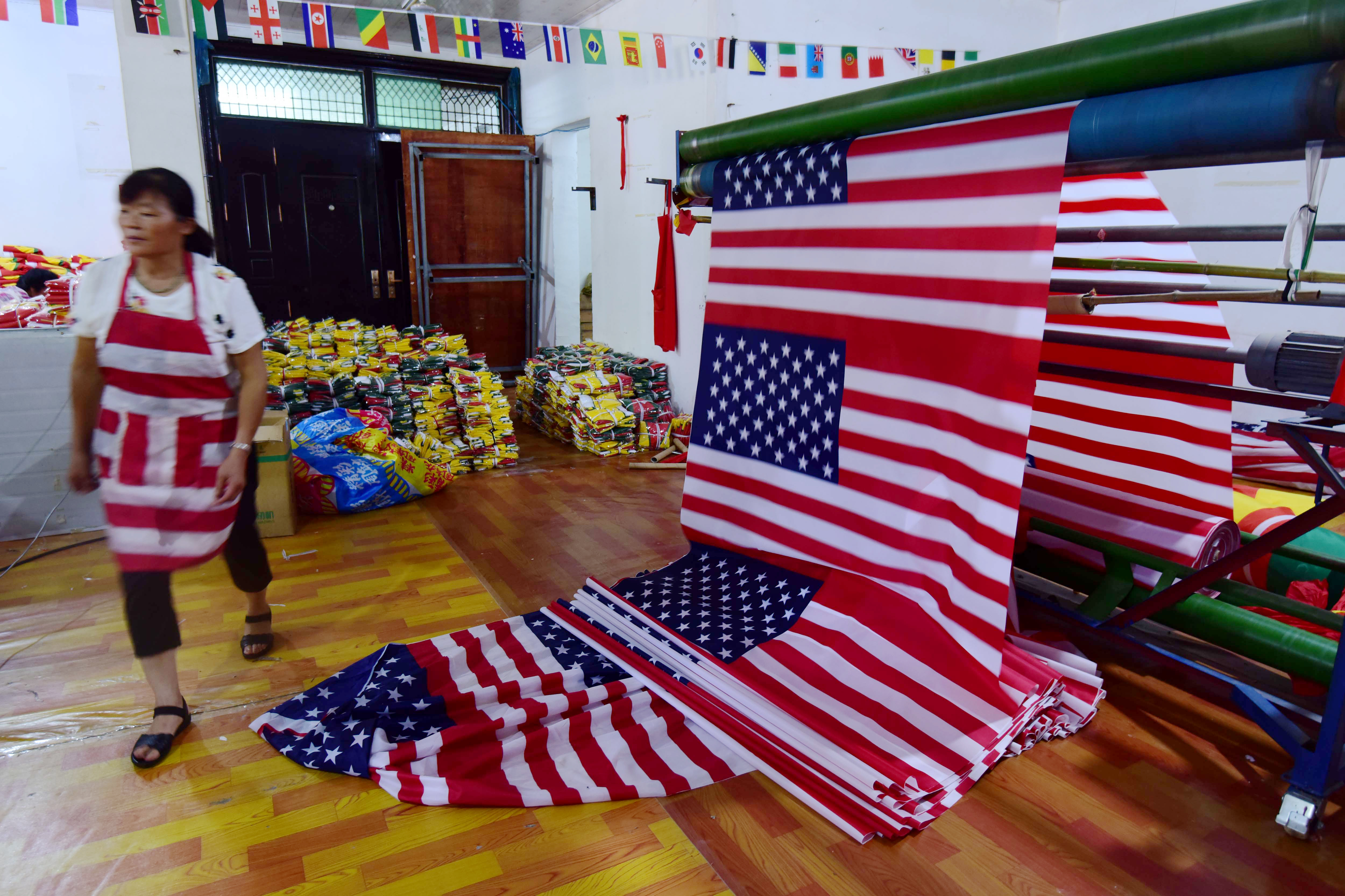"""A Chinese employee walks past newly made U.S. flags at a factory in Fuyang in China's eastern Anhui province, July 13, 2018. As the U.S.-China trade war rages, a factory set amid corn and mulberry fields in central China stitches together U.S. and """"T..."""