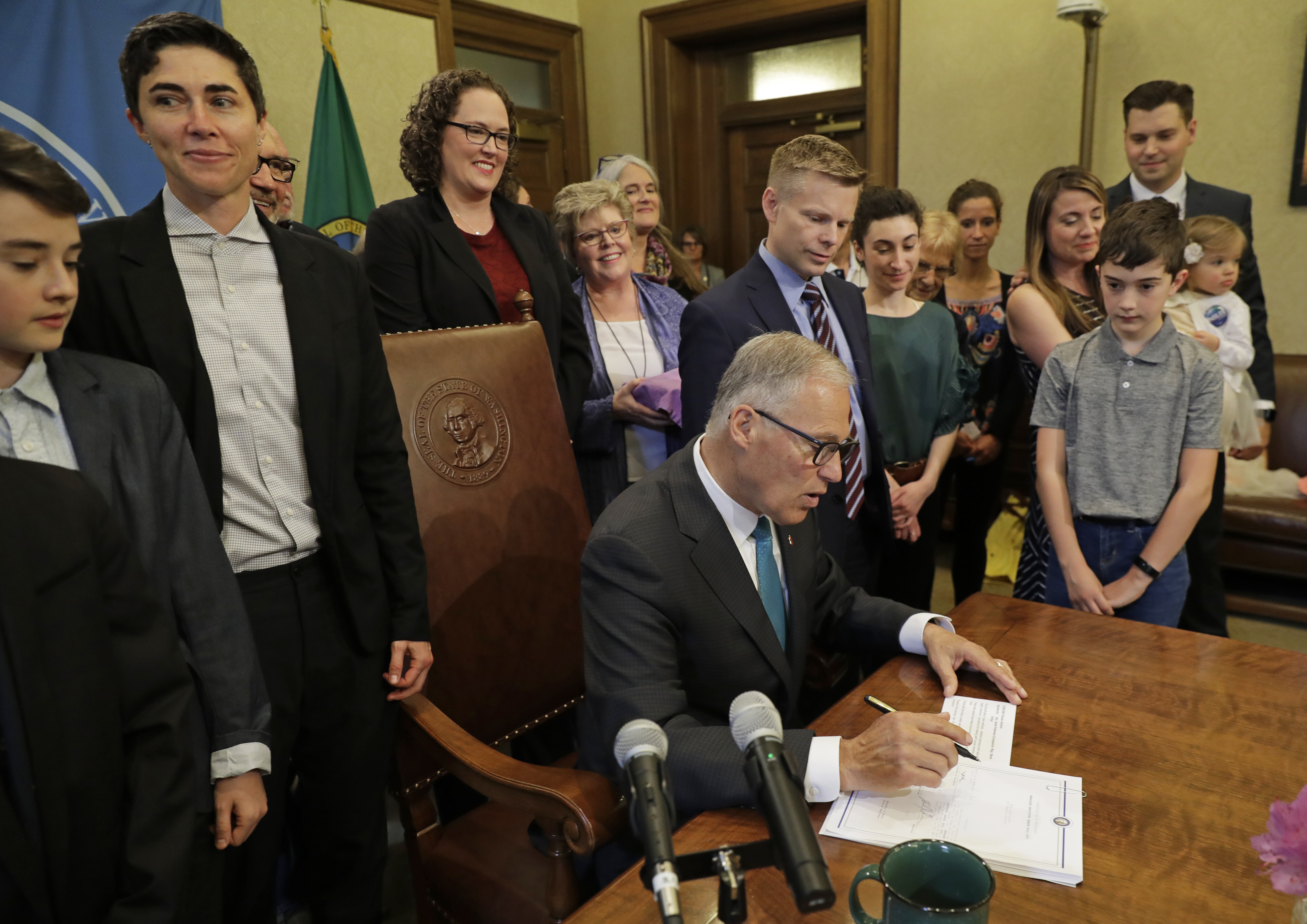 """Washington Gov. Jay Inslee signs a bill into law at the Capitol in Olympia, Wash., May 21, 2019, that allows licensed facilities to offer """"natural organic reduction,"""" which turns a body, mixed with substances such as wood chips and straw, into soil i..."""