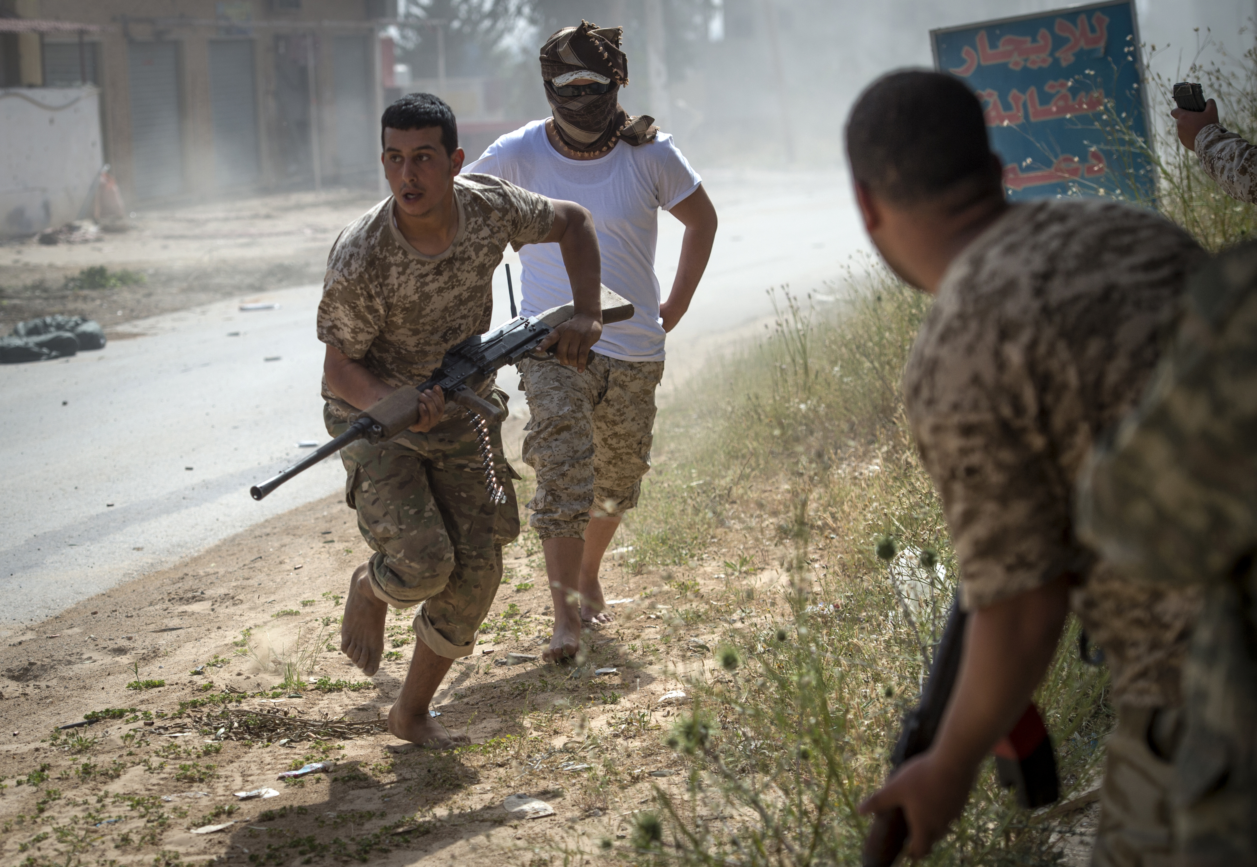 Fighters loyal to the internationally recognized Government of National Accord (GNA) run for cover during clashes with forces loyal to strongman Khalifa Haftar south of the capital Tripoli's suburb of Ain Zara, on April 25, 2019.