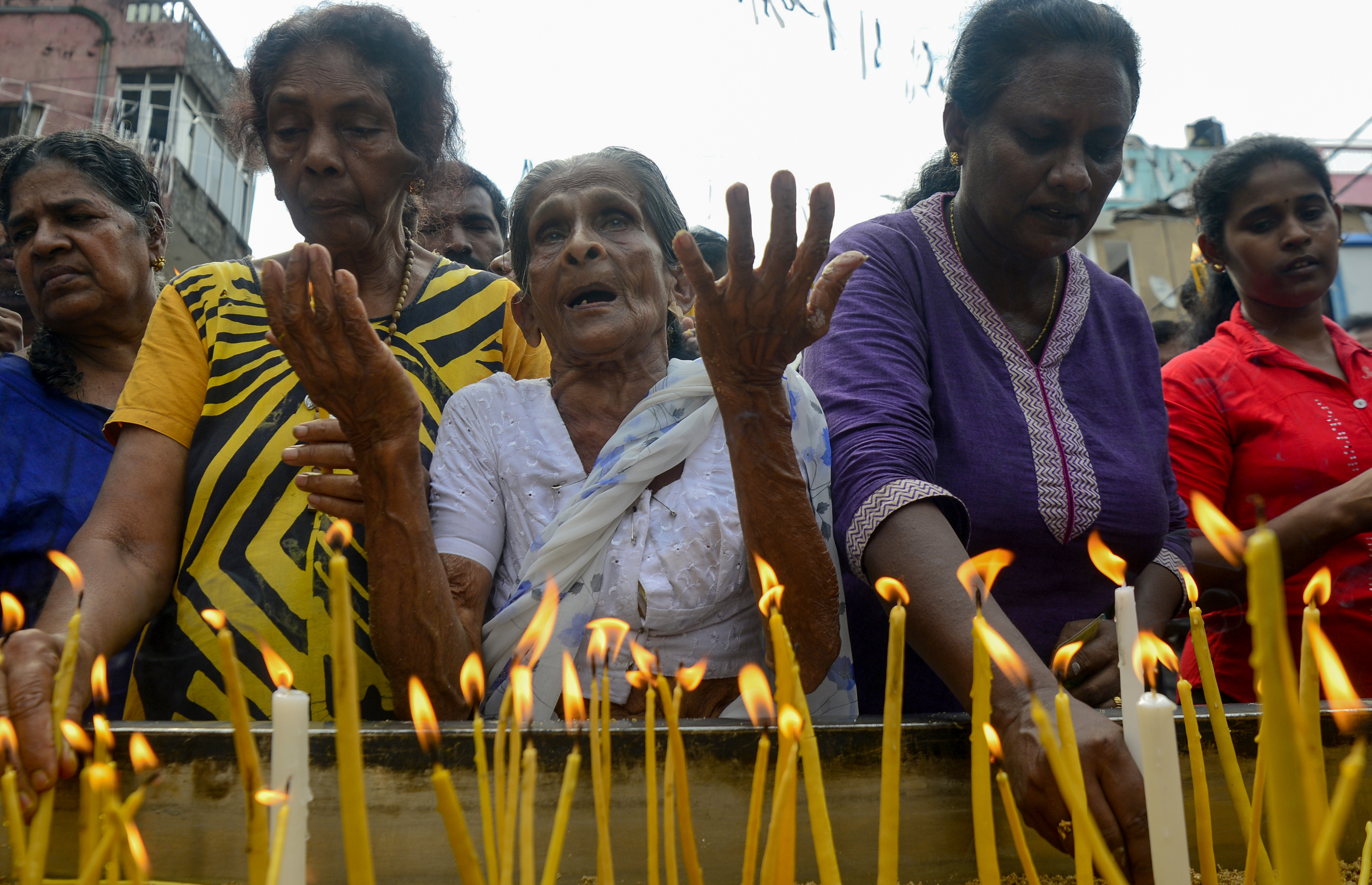 Sri Lankan Christian devotees light candles as they pray at a barricade near St. Anthony's Shrine in Colombo, April 28, 2019, a week after a series of bomb blasts targeting churches and luxury hotels on Easter Sunday in Sri Lanka.