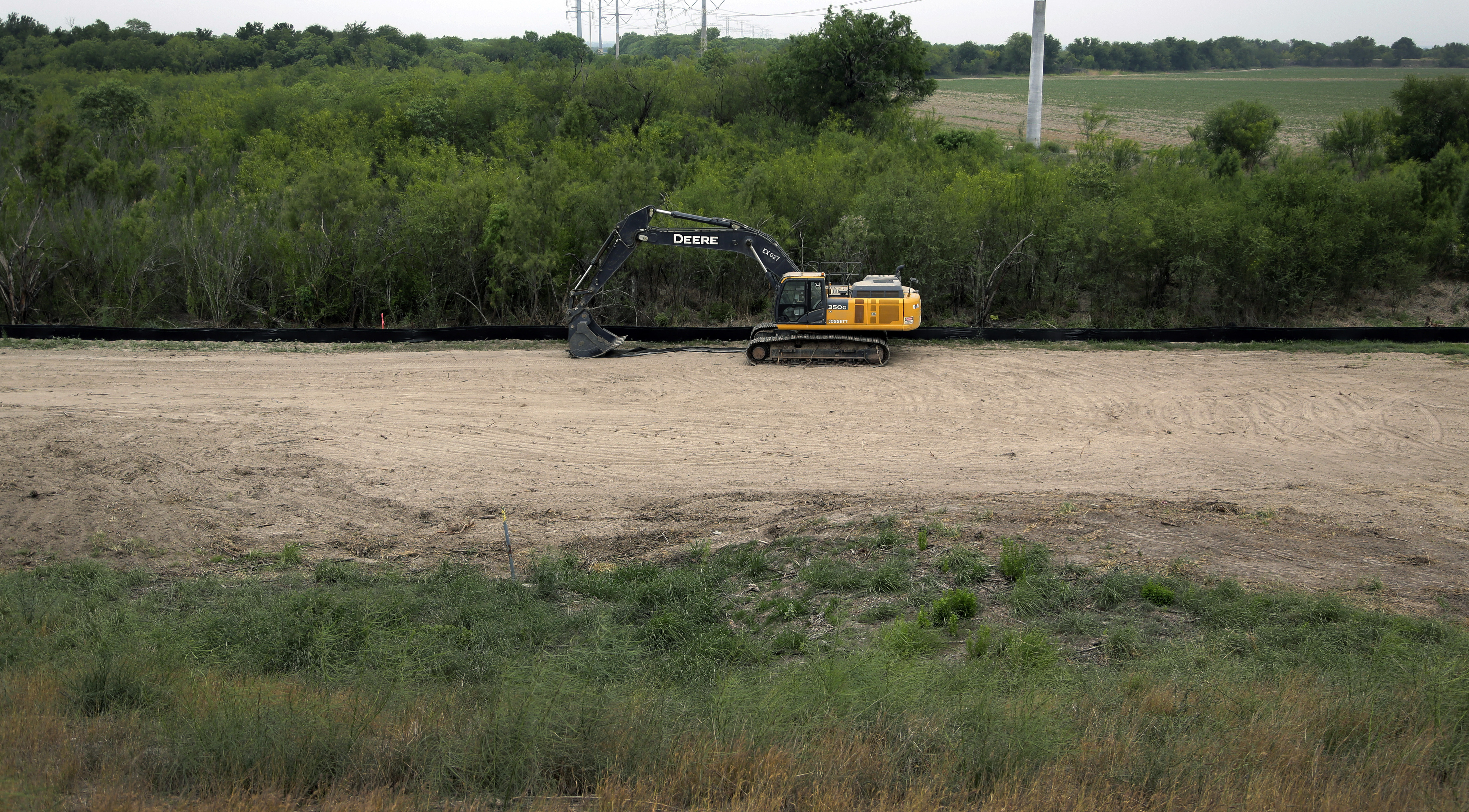 Construction equipment sets in an area of demolished trees and brush, April 29, 2019, where construction is set to begin soon, in Mission, Texas.