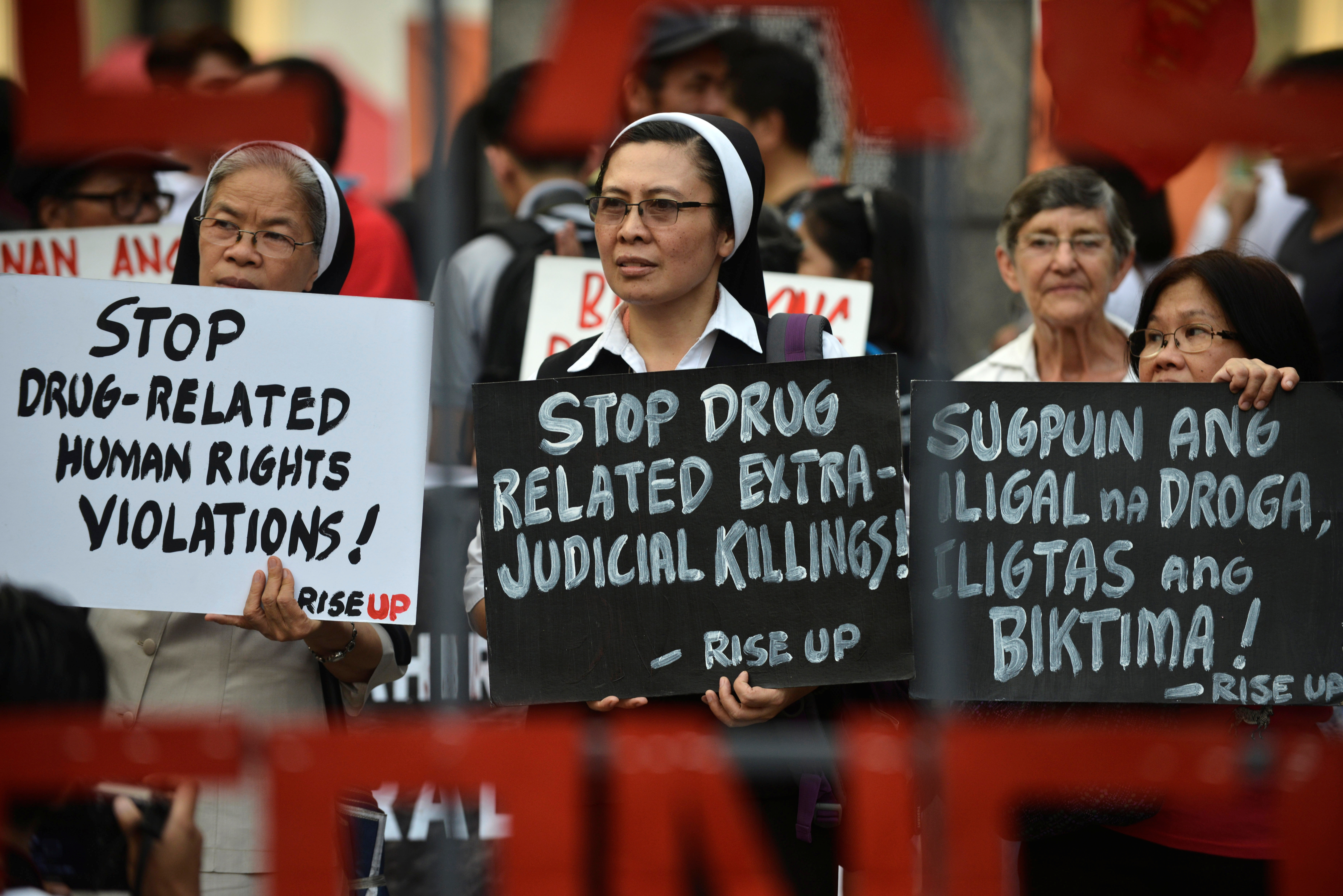 FILE - Catholic nuns hold placards as they protest against what organizers say are drug-related extrajudicial killings, during International Human Rights Day in Manila, Philippines, Dec. 10, 2016.