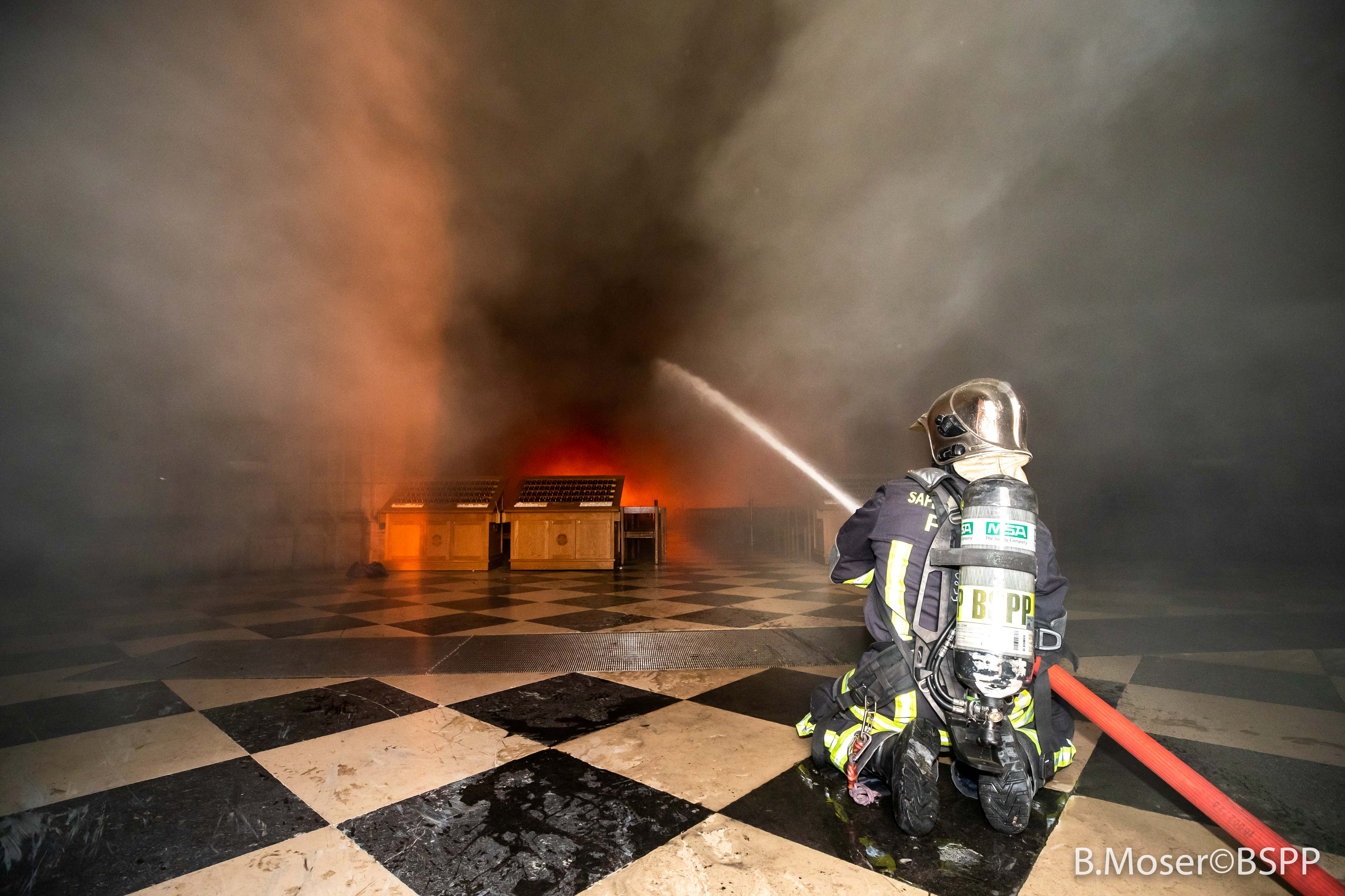 A Paris fire brigade member sprays water on flames inside the Notre Dame-Cathedral, in this image provided by the Paris Fire Brigade, after a fire broke out, in Paris, France, April 15, 2019.