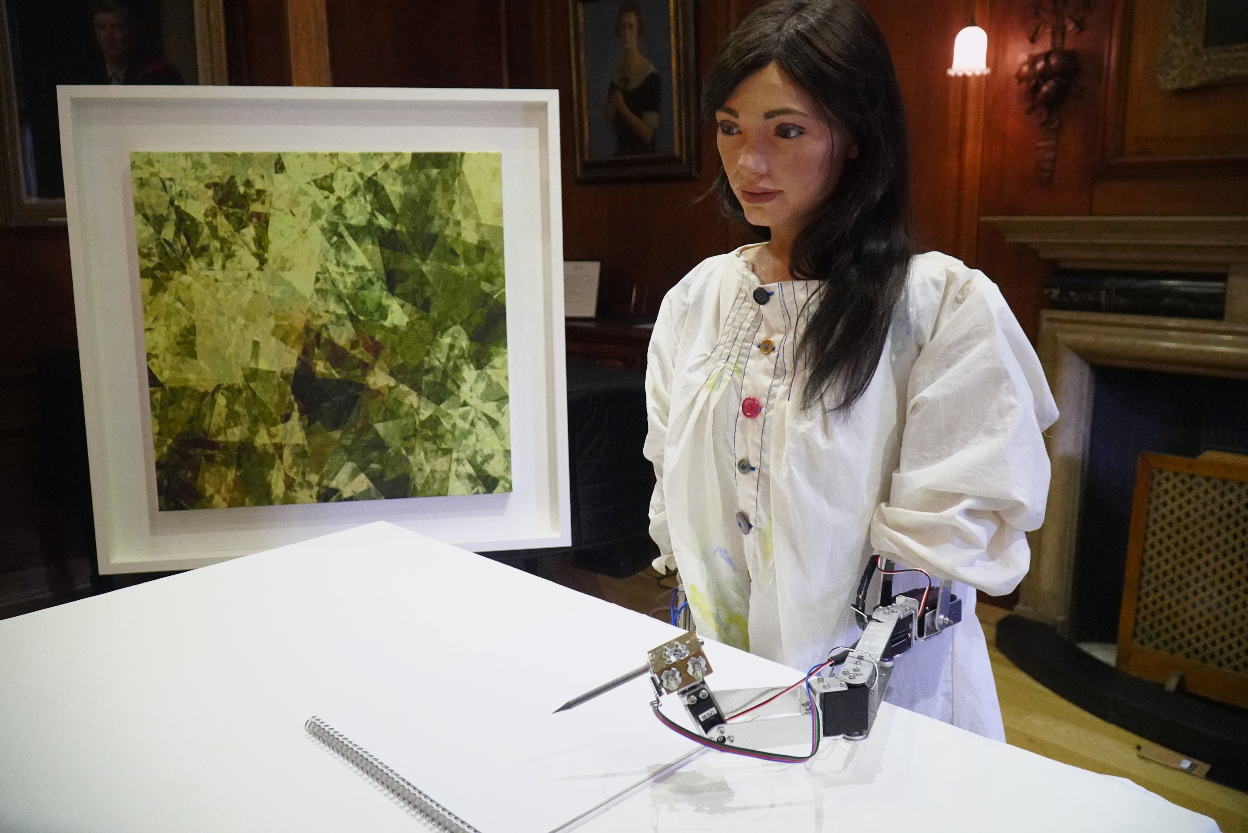 Robot artist 'Ai-Da' sketches using a pencil attached to her robotic arm, while standing next to a painting based on her computer vision data when run through algorithms developed by computer scientists in Oxford, Britain, June 4, 2019.