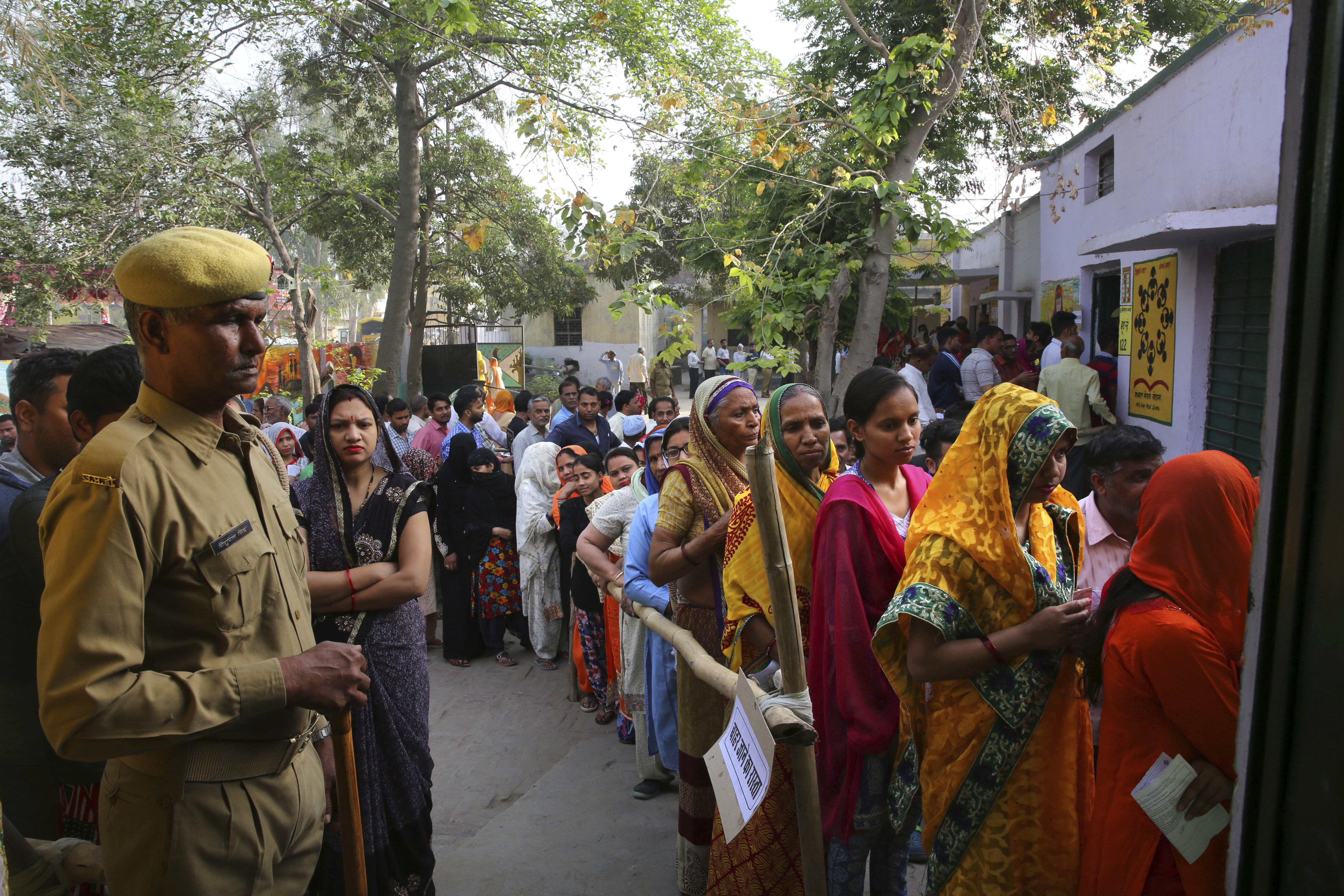 Indians stand in queues to cast their votes at a polling booth for the first phase of general elections, near Ghaziabad, India, April 11, 2019.