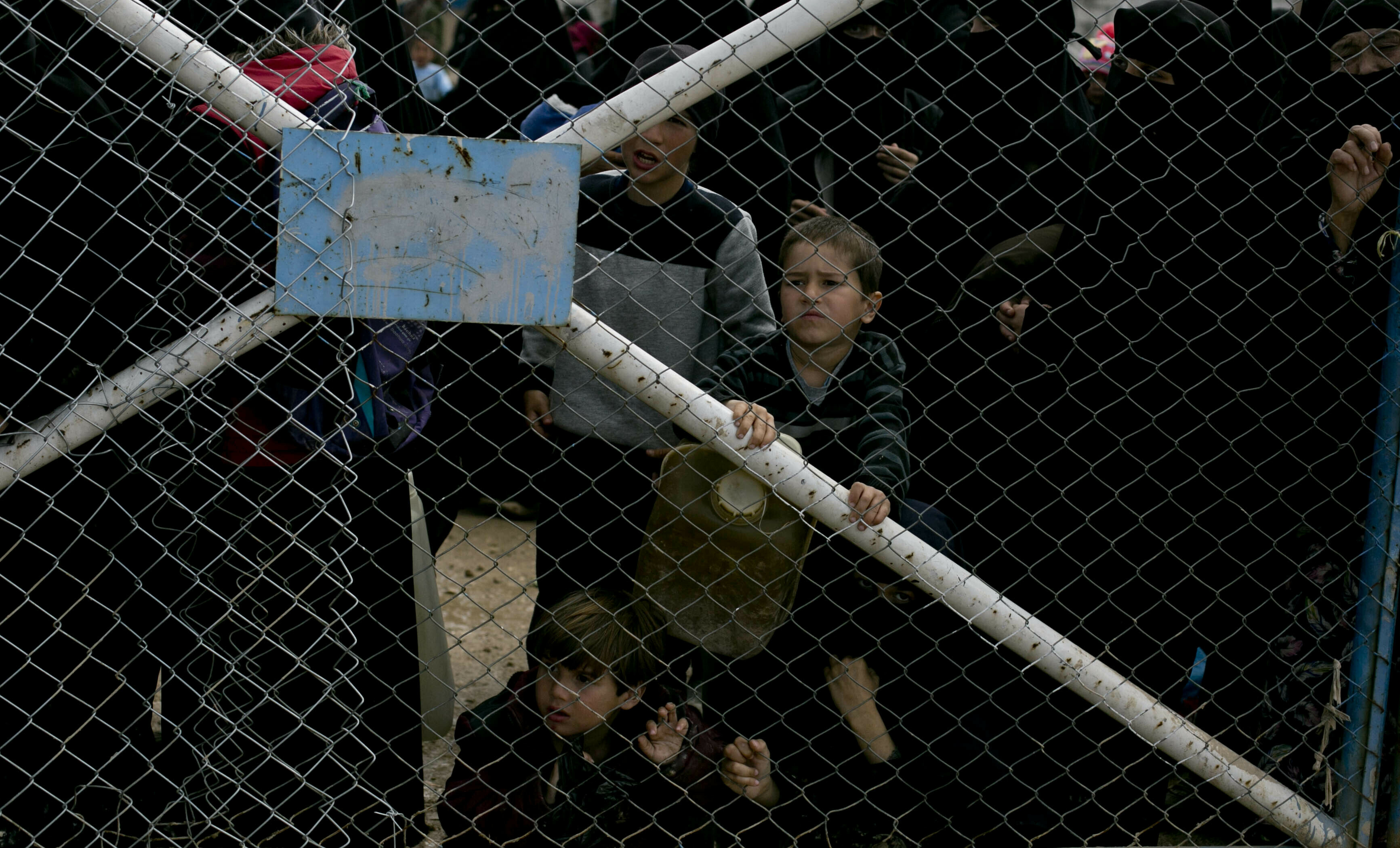 FILE - Children peer from the gate that closes off the section for foreign families who live in the Islamic State group's so-called caliphate, at al-Hol camp in Hassakeh province, Syria, March 31, 2019.