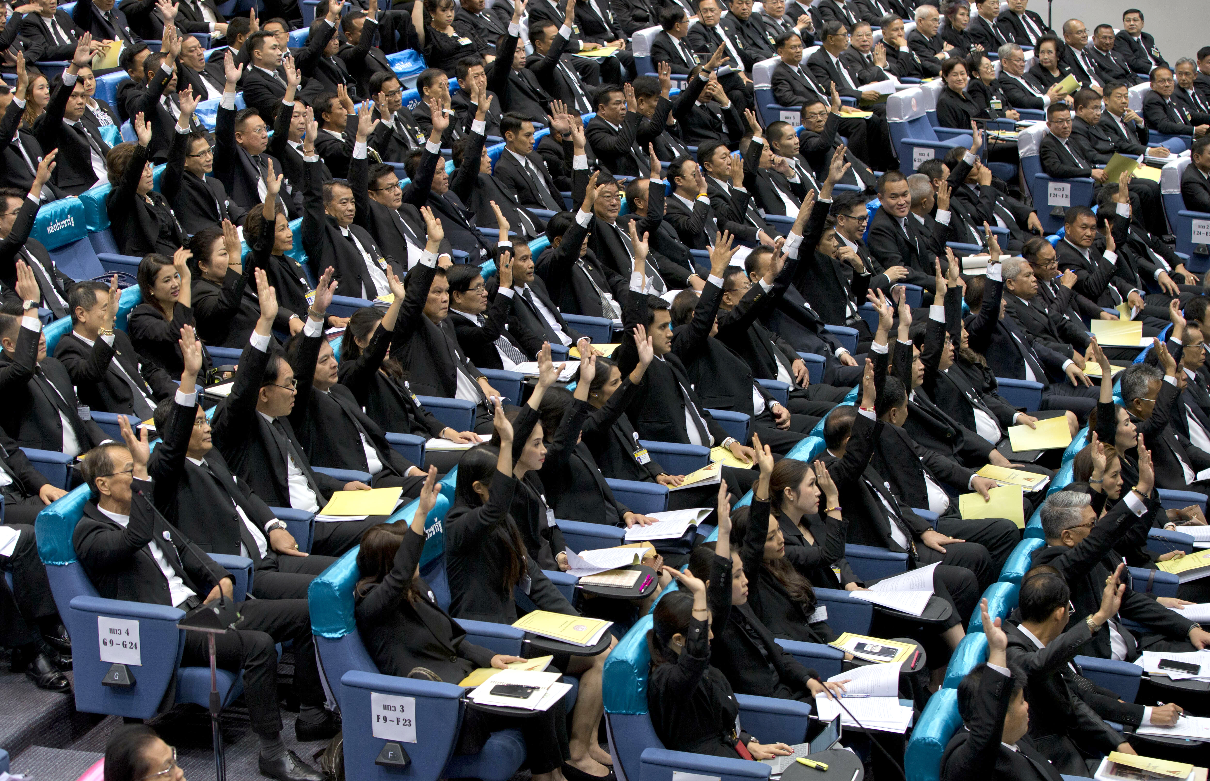 Members of the parliament representing the military-backed Palang Pracharath party raise their hands, approving the nomination of Prayuth Chan-ocha as Thailand's prime minister during a session in Bangkok, Thailand, June 5, 2019.