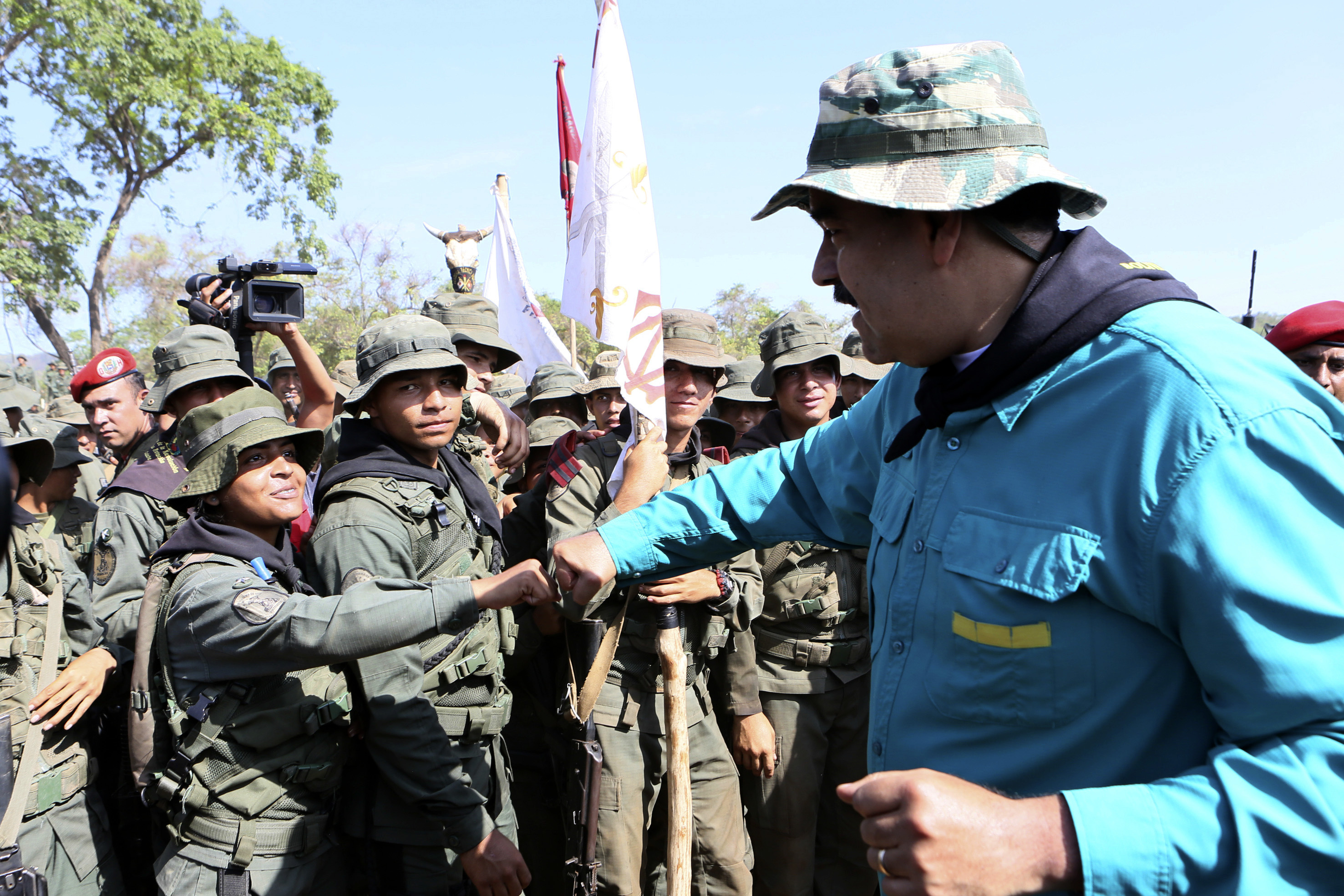 In this handout photo released by Miraflores Press Office, Venezuela's President Nicolas Maduro fist bumps with a cadet at the G/J José Laurencio Silva military training center in the state of Cojedes, Venezuela, May 4, 2019.