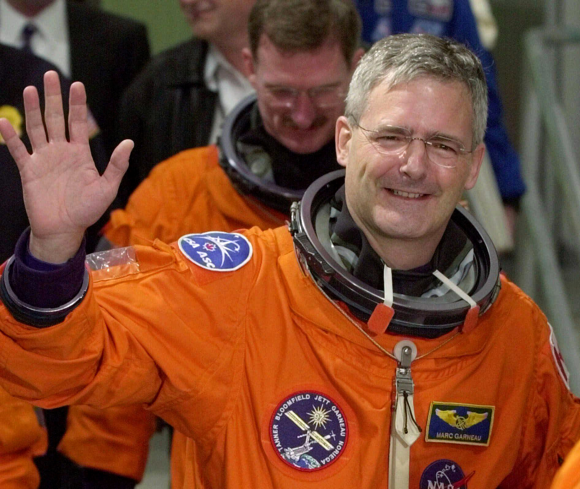 File-This Nov. 30, 2000 file photo shows mission specialist Marc Garneau of Canada waving to photographers as he leaves the Operations and Checkout Building.